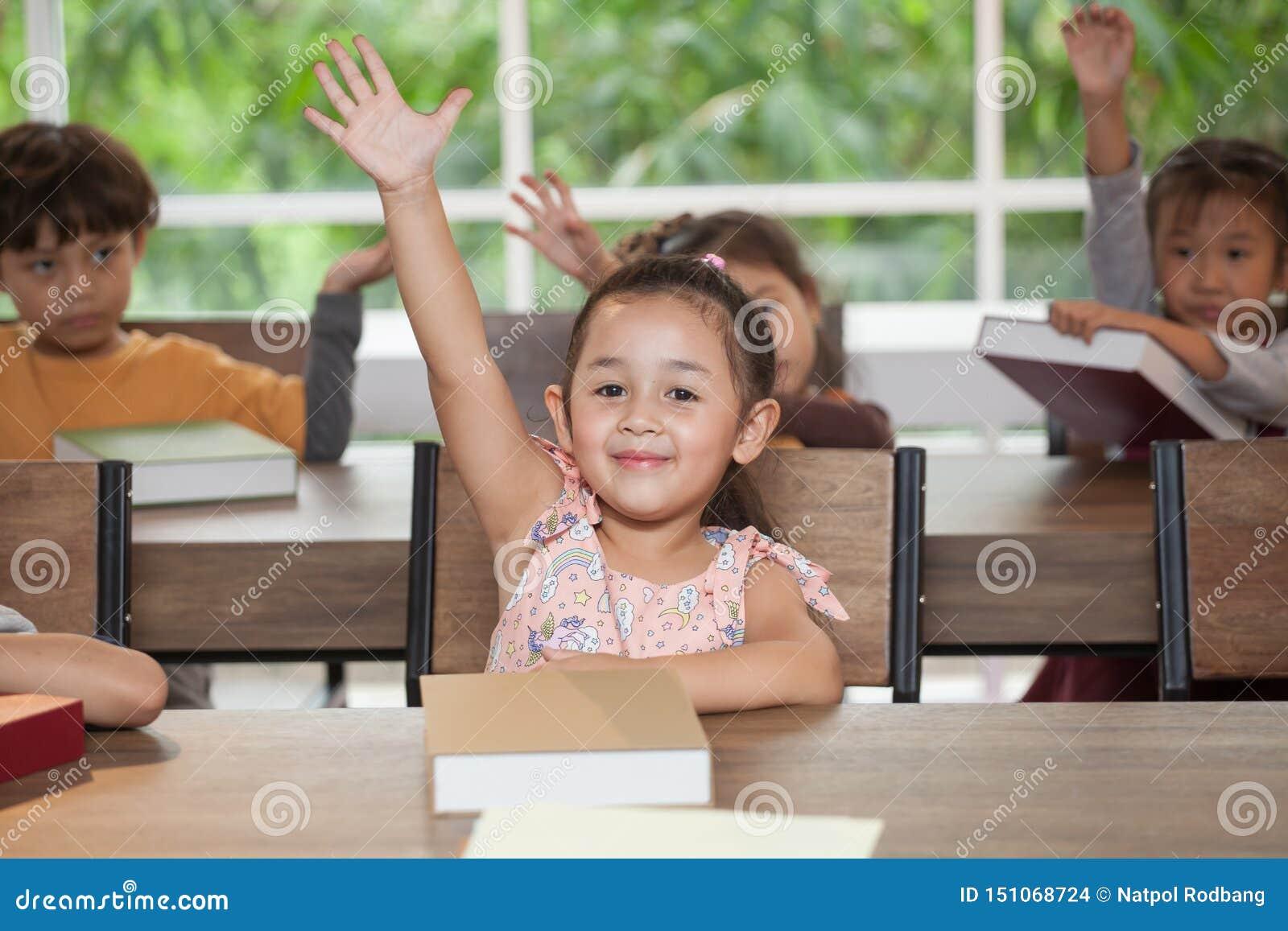 Gullig liten flickastudent för grupp som lyfter händer i klassrumskola snilleungehand upp stor id? klyftigt sammanträde för barn