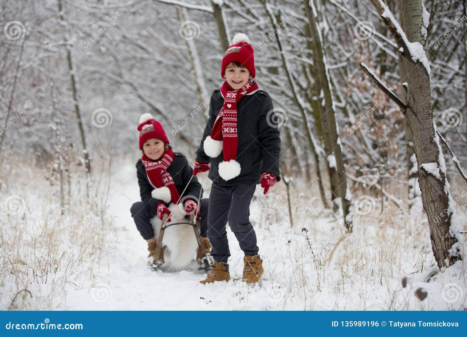 Gullig liten litet barnpojke och hans äldre bröder som utomhus spelar med snö på en vinterdag