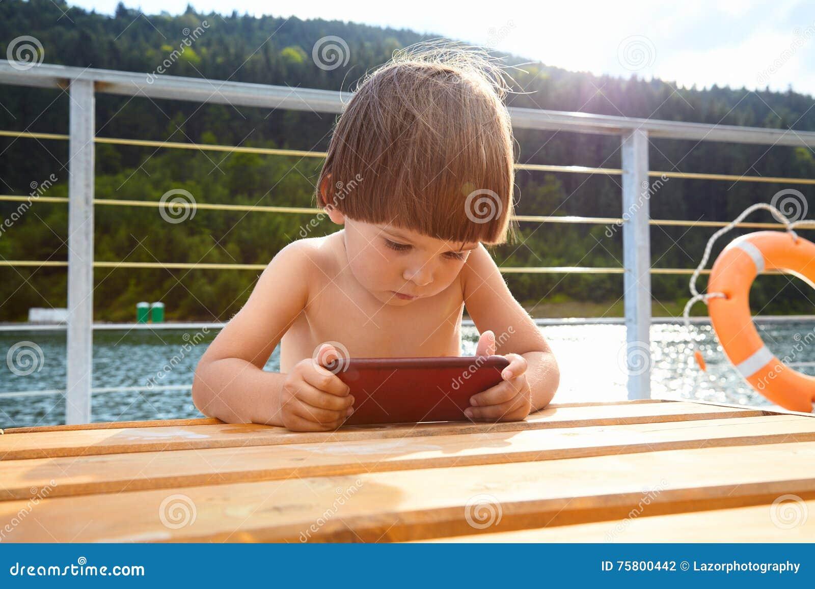 Ståenden av den gulliga lilla litet barnpojken som använder hans smarta  telefon som spelar spelar på stranden nära bergsjön på den utomhus- soliga  dagen på ... 84b4116c6c8f3