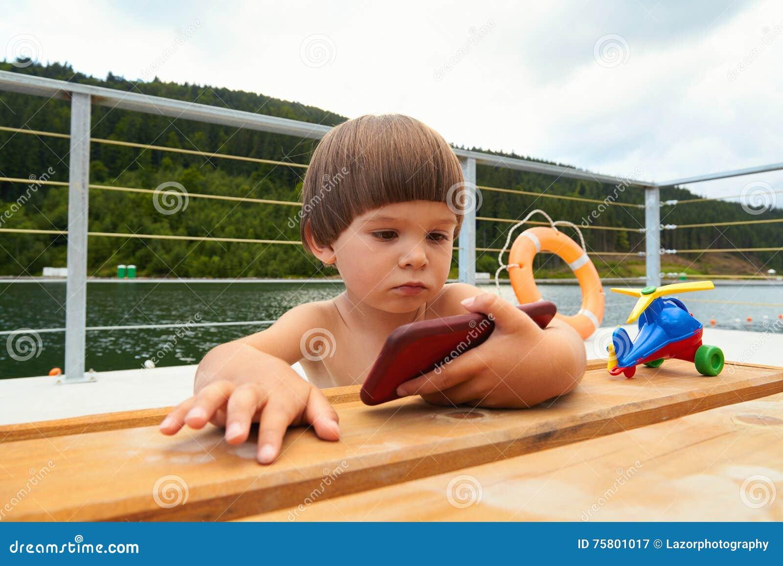 Ståenden av den allvarliga gulliga lilla litet barnpojken som håller ögonen  på på hans smarta telefon som spelar spelar på stranden nära bergsjön på  den ... 24f1c10eca37b