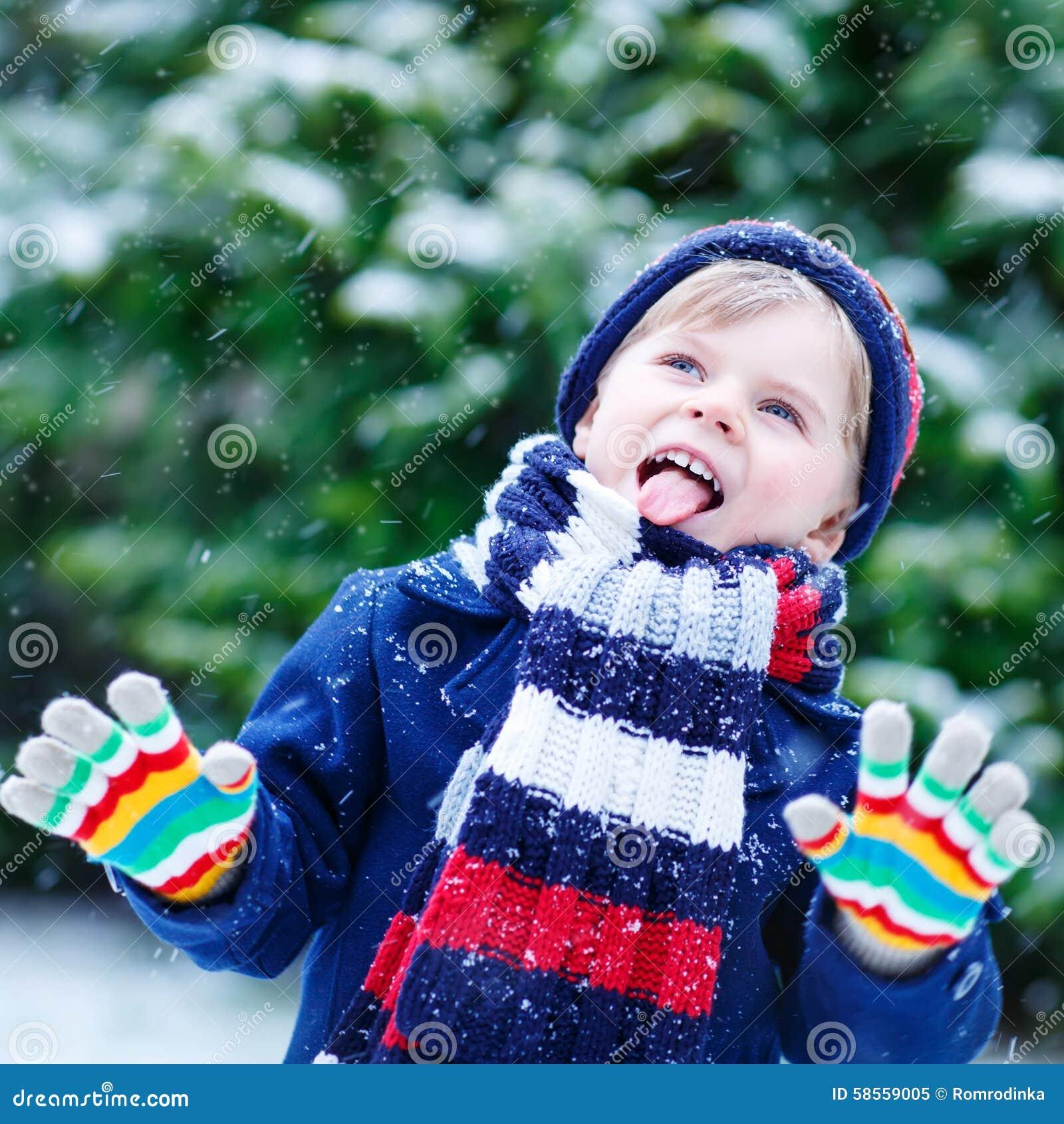 Gullig liten rolig pojke i färgrik vinterkläder som har gyckel med