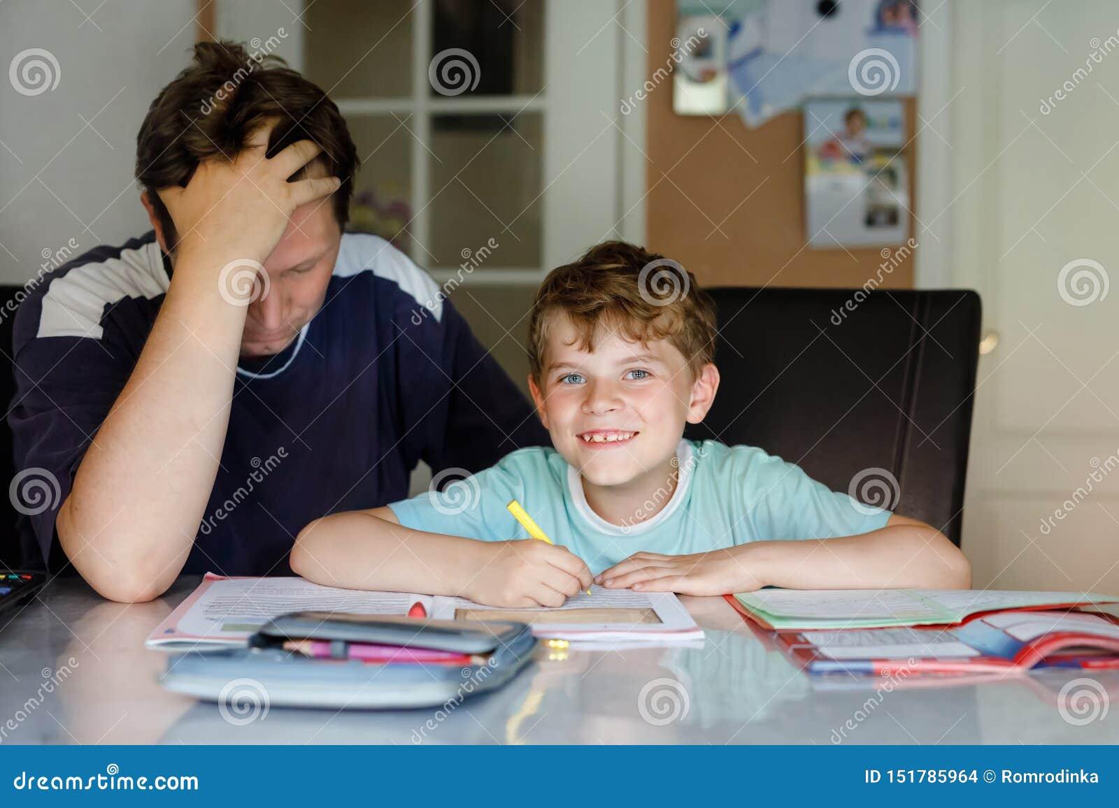Gullig liten skolaungepojke hemma som gör läxa med farsan Handstil för litet barn med färgrika blyertspennor, hjälpa för fader