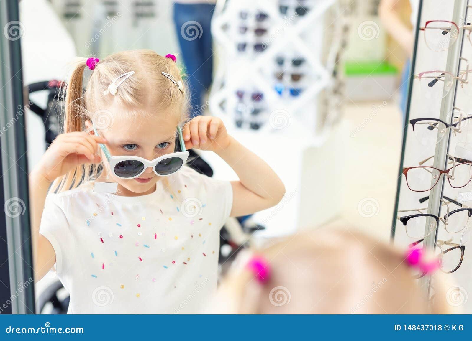 Gullig liten ung caucasian blond flicka som p? f?rs?ker och framme v?ljer solglas?gon av spegeln p? det optiska eyewearlagret _