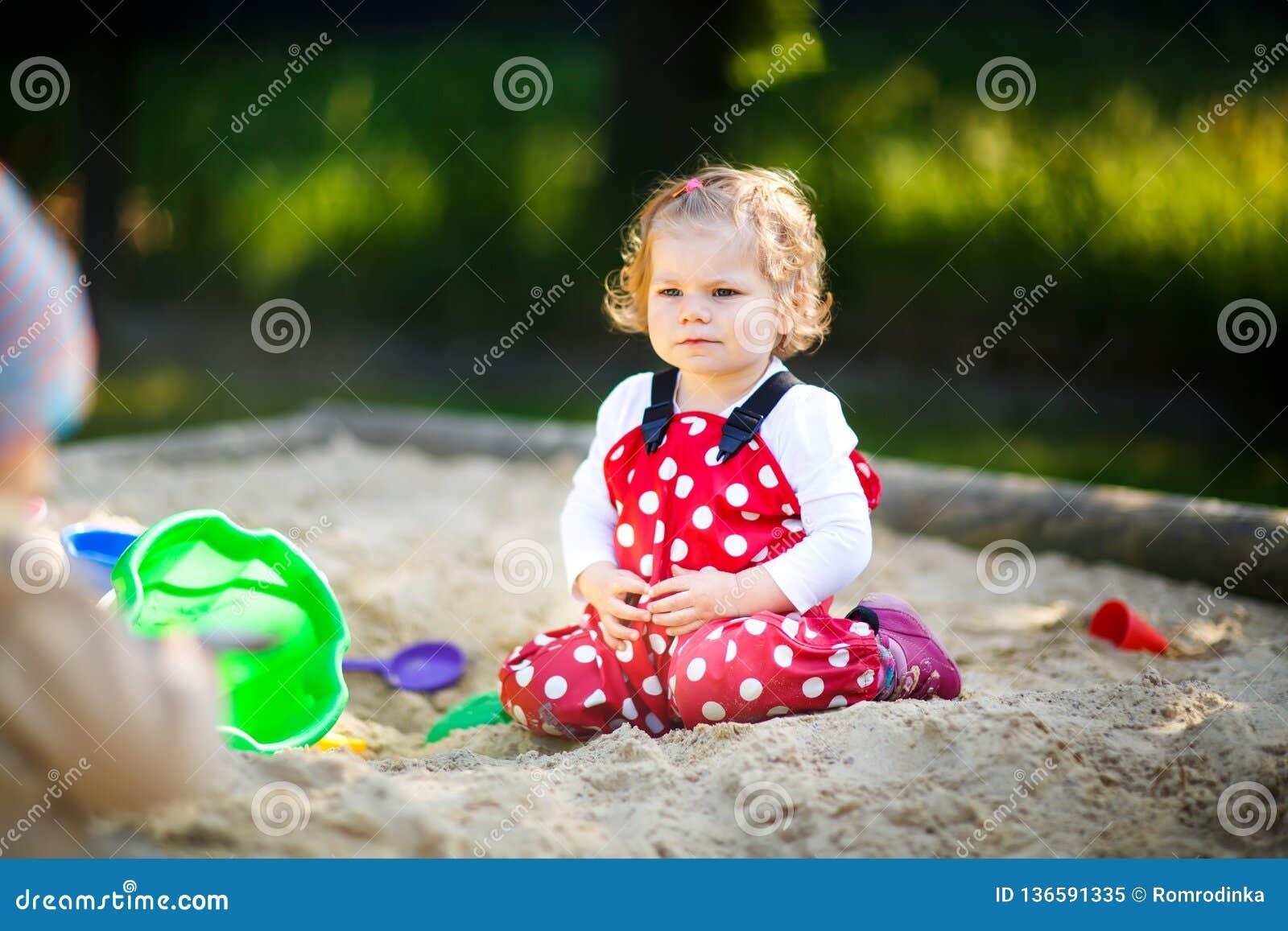 Gullig litet barnflicka som spelar i sand på utomhus- lekplats Härligt behandla som ett barn i byxa för rött gummi som har gyckel