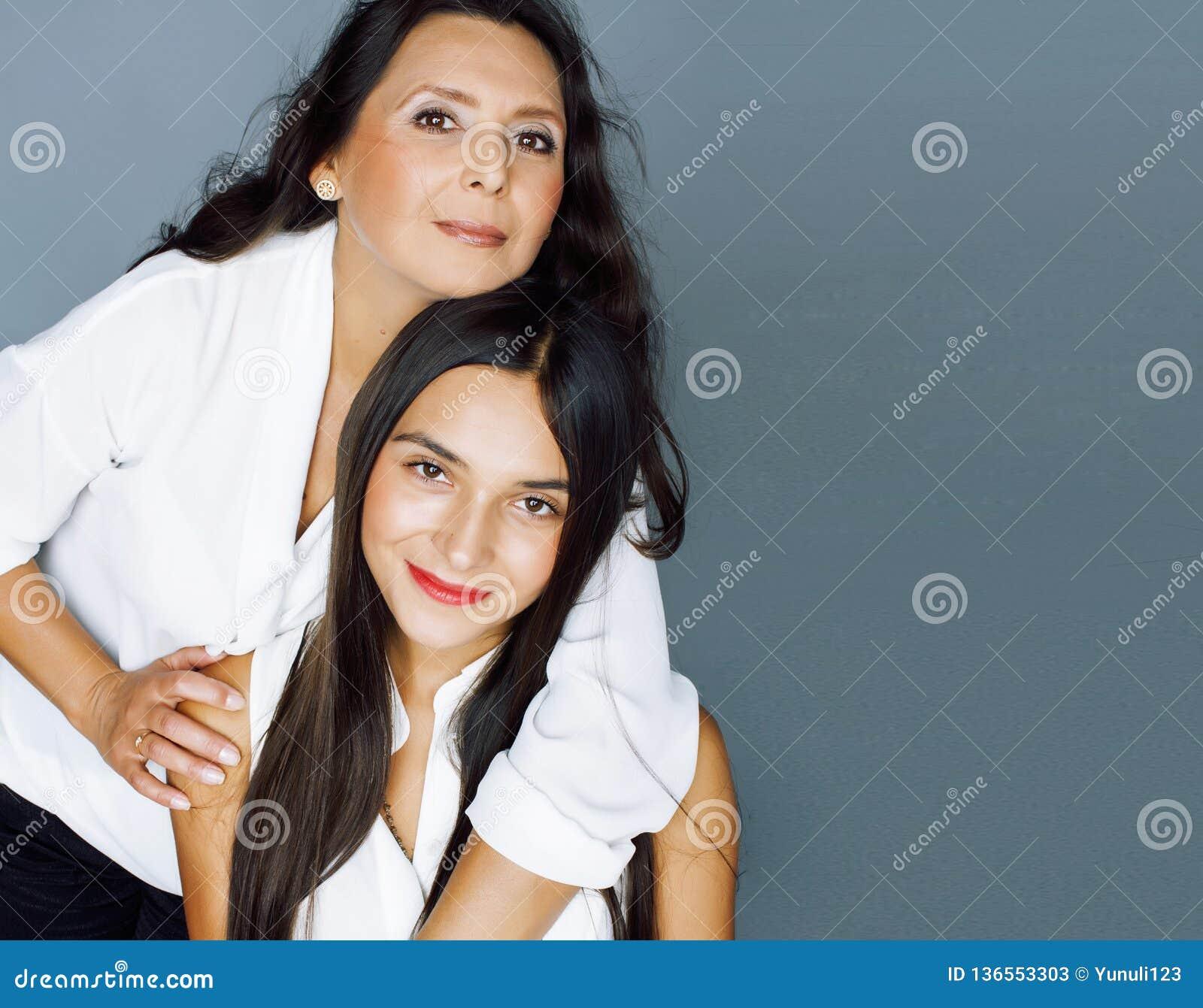 Gullig nätt tonårig dotter med den mogna modern som kramar, modest
