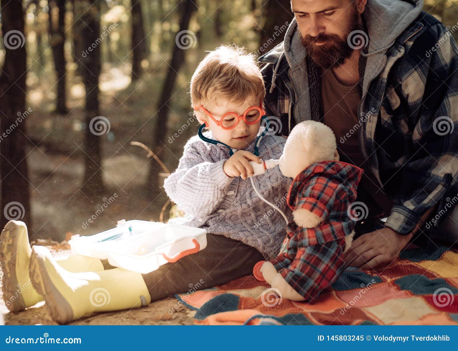 Gullig pojke med nästorkaren nära höstträd Fader- och barnsonen i h?st parkerar att ha gyckel och att skratta lycklig familj