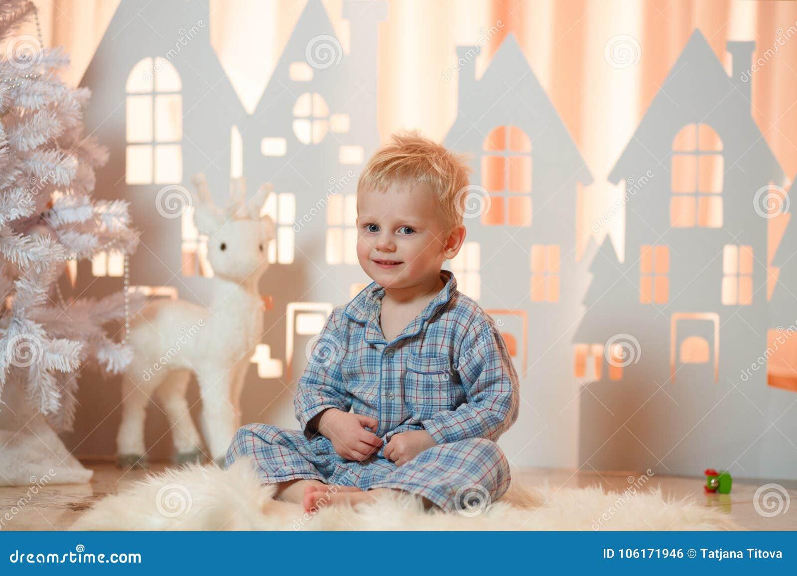Gullig pys för blont hår i sleepwear nära hus för julleksakpapper
