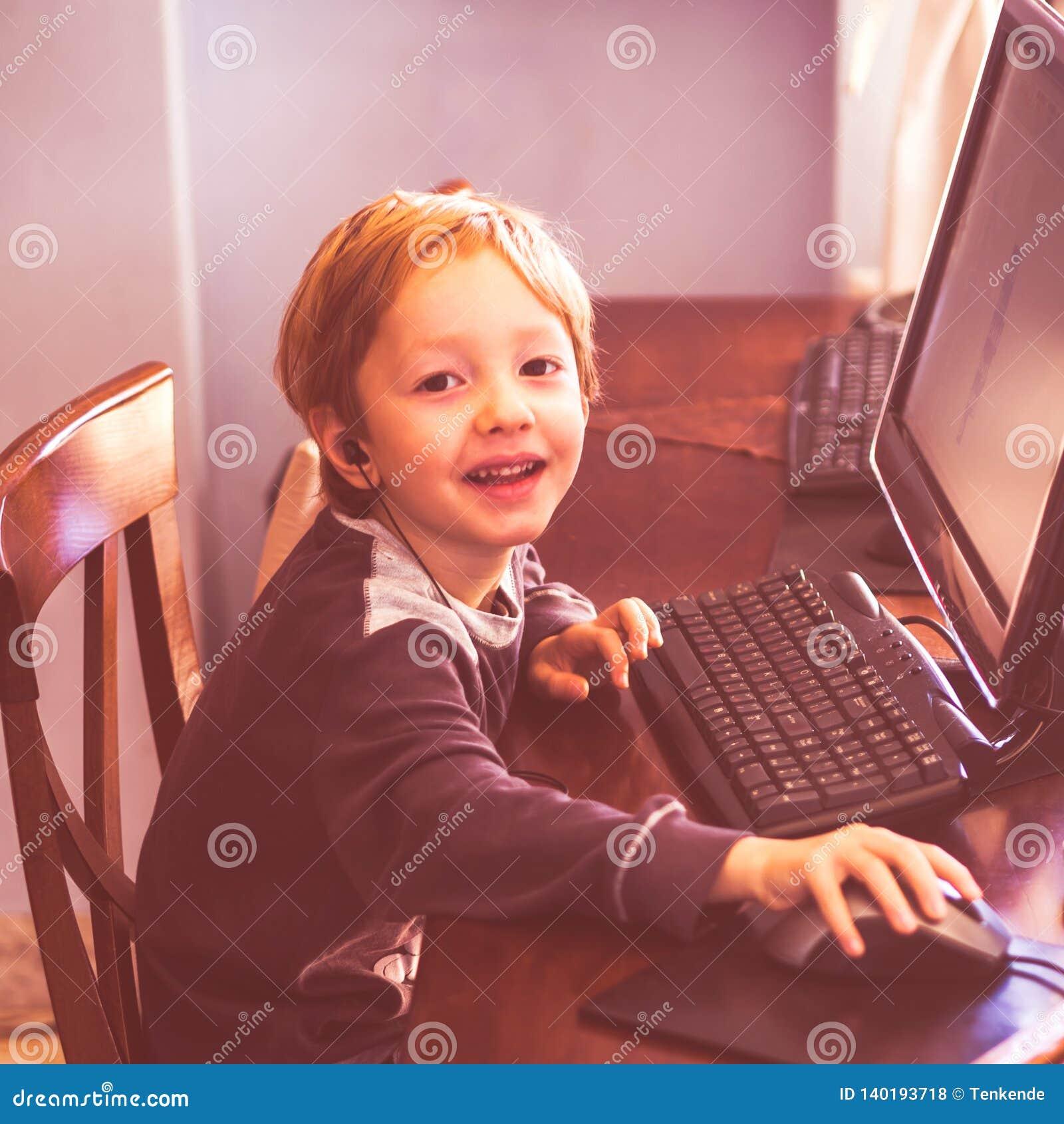Gullig pys som spelar på datoren med hörlurar med mikrofon