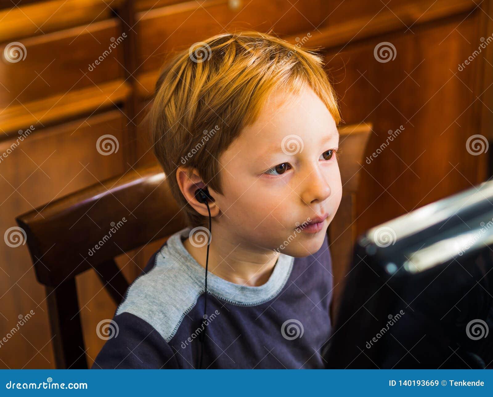 Gullig pys som spelar på den koncentrerade PC:n