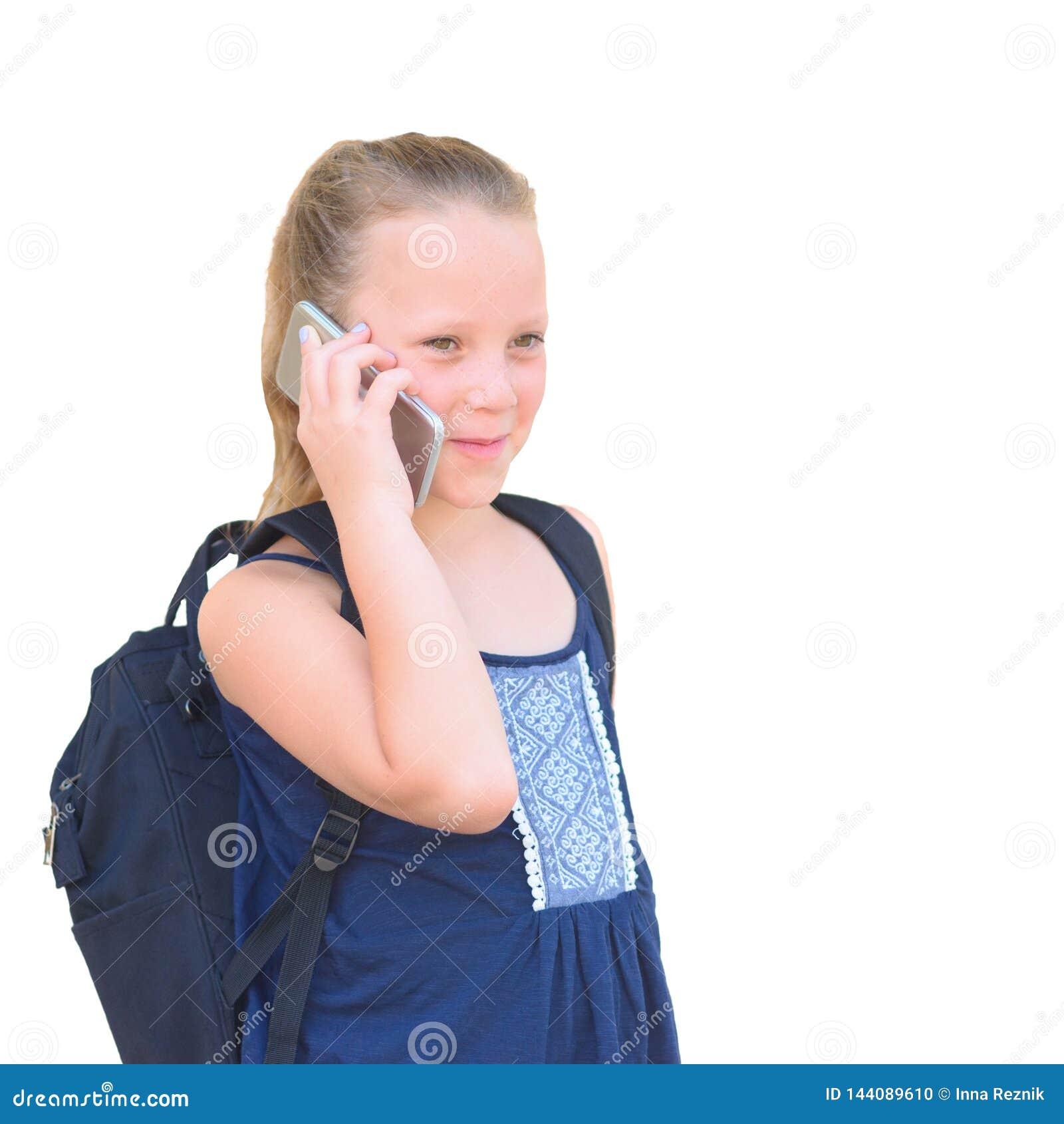 Gullig skolflicka med ryggsäcken som talar på mobiltelefon isolerad bild