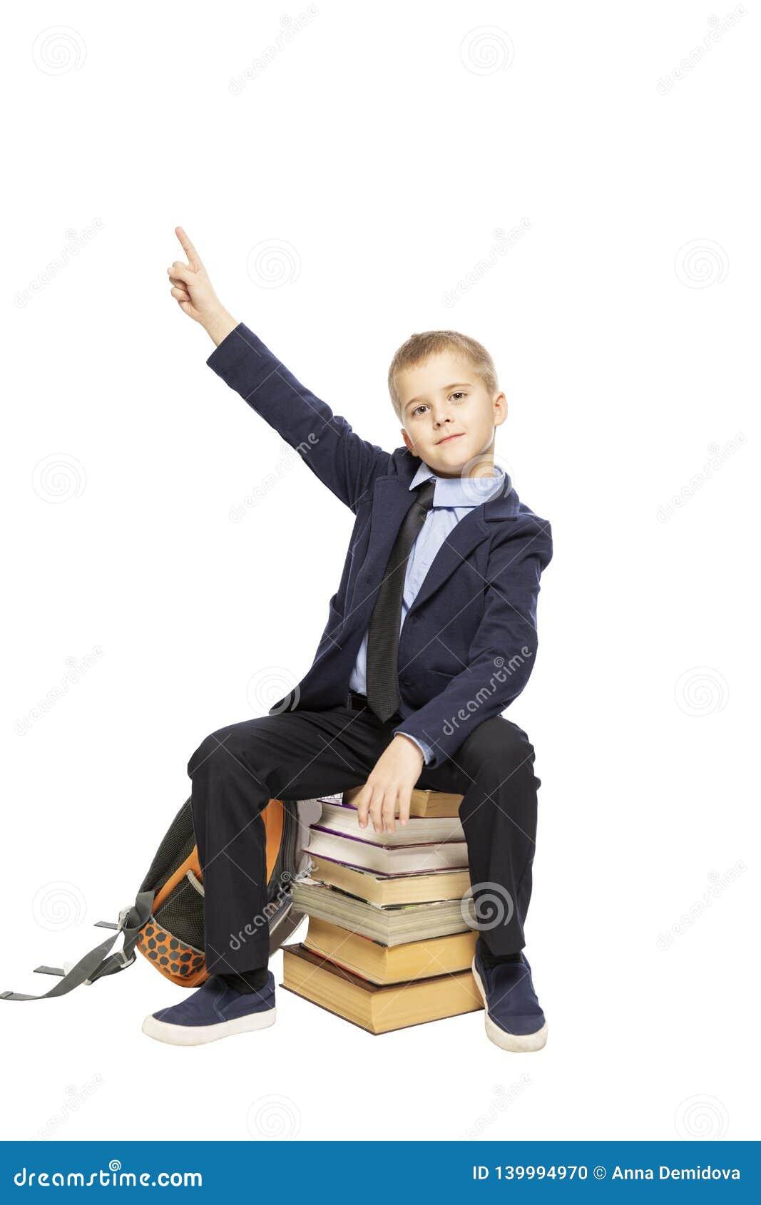Gullig skolpojke som sitter på böcker och visar upp tummen, isolerat på vit bakgrund