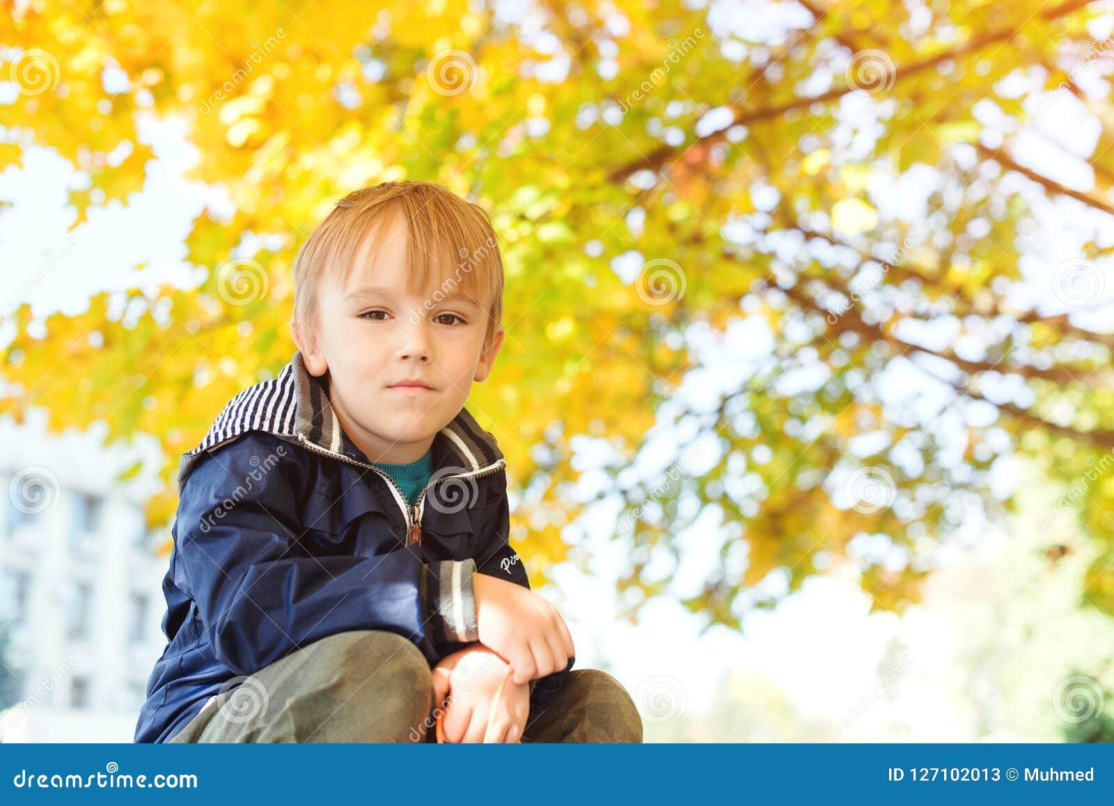 Gullig stilig le pysstående Den stilfulla pojken som tycker om färgglad höst, parkerar säsong för bana för höstfallskog Sund och