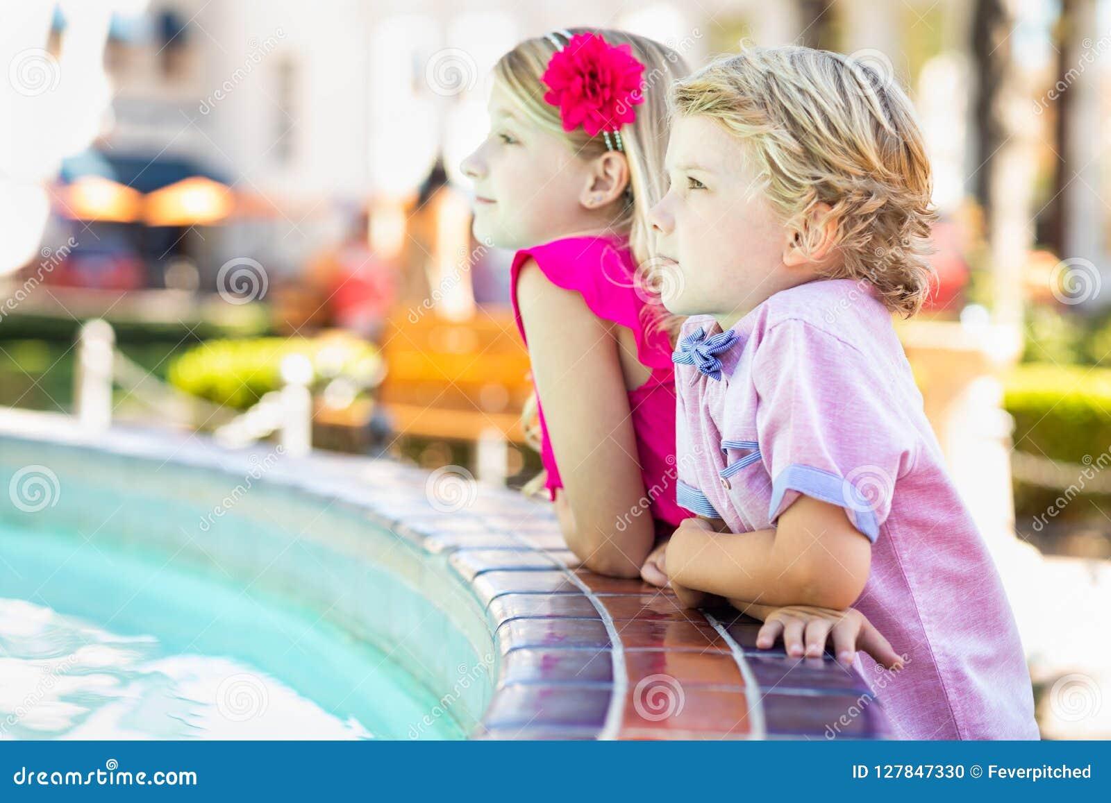 Gullig ung Caucasian syskongrupp Enjoying en springbrunn på