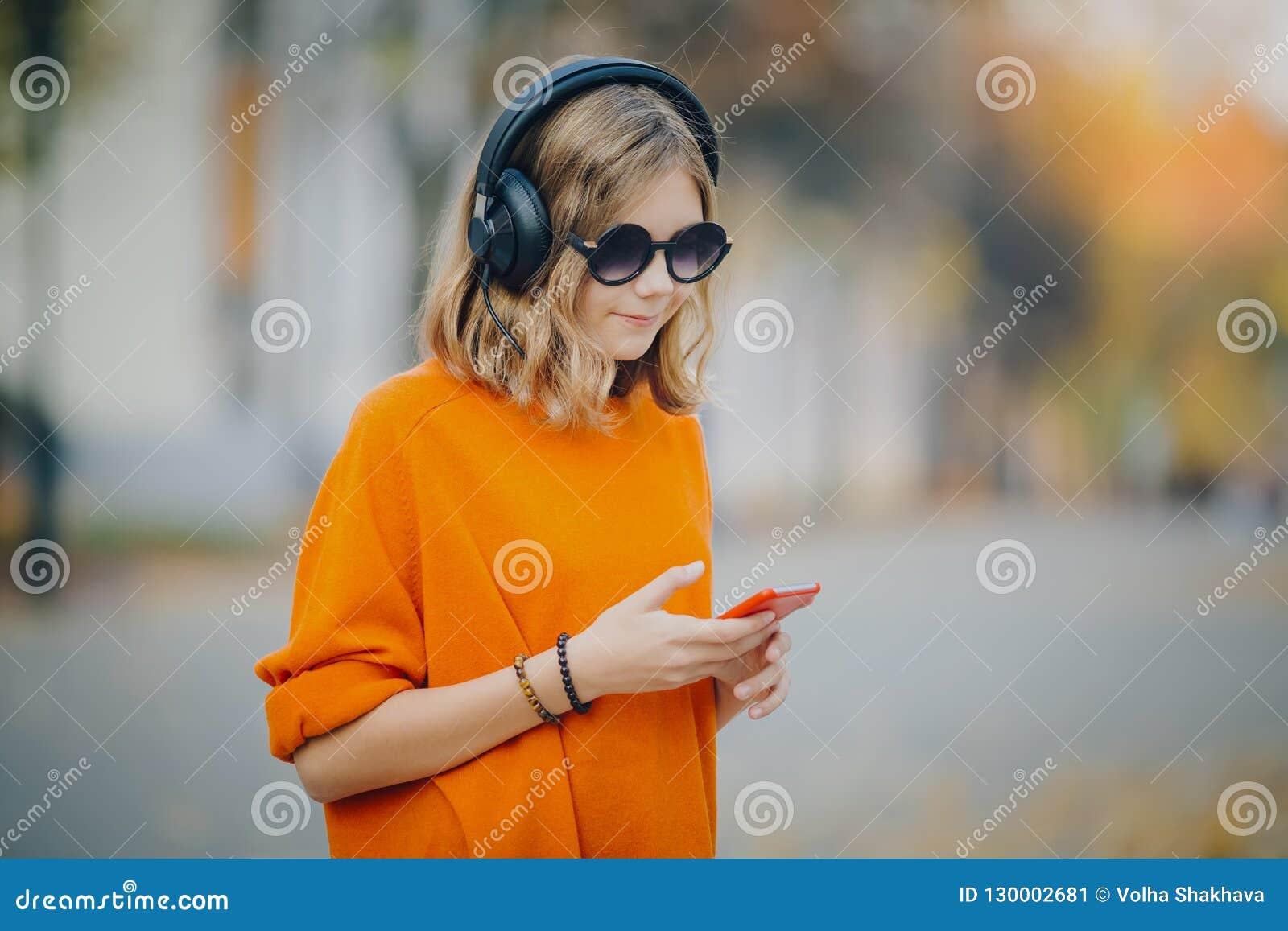 Gullig ung flicka som går ner den gamla stadsgatan och lyssnande musik i hörlurar, stads- stil, tonårig håll för stilfull hipster