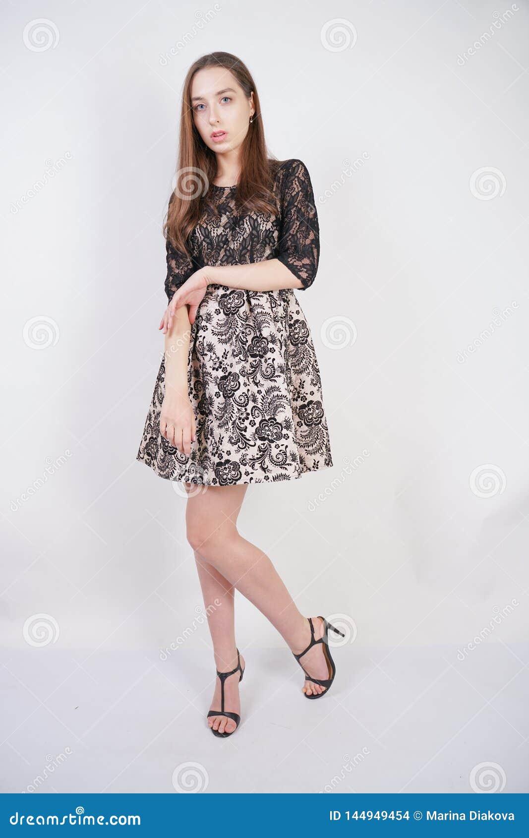 Gullig ung flickadans i kort aftonklänning på vit bakgrund i studio