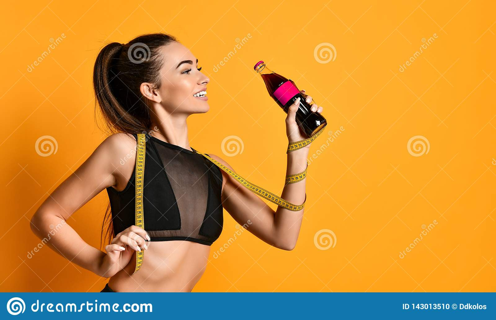 Gullig ung konditionflicka i svarta dräktblickar in i kameran och att hålla det mäta bandet och flaskan på handen