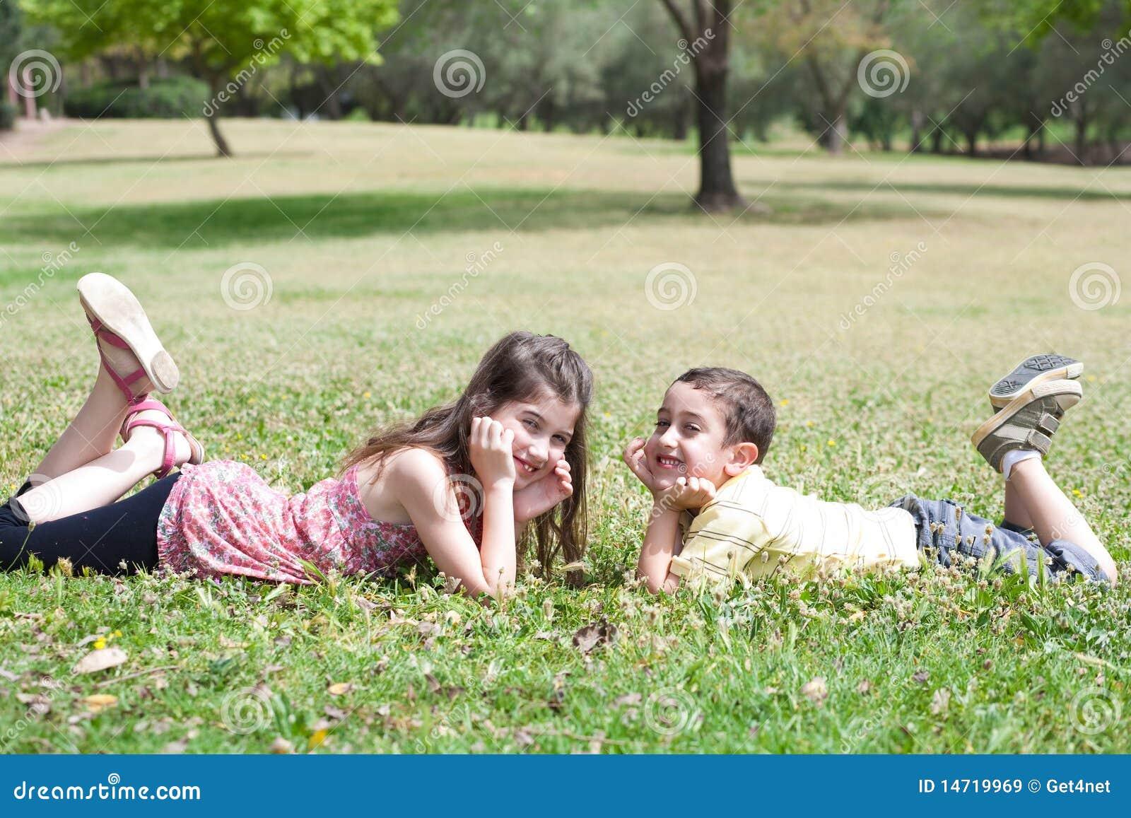 Gulliga barn gräs ner grön lie