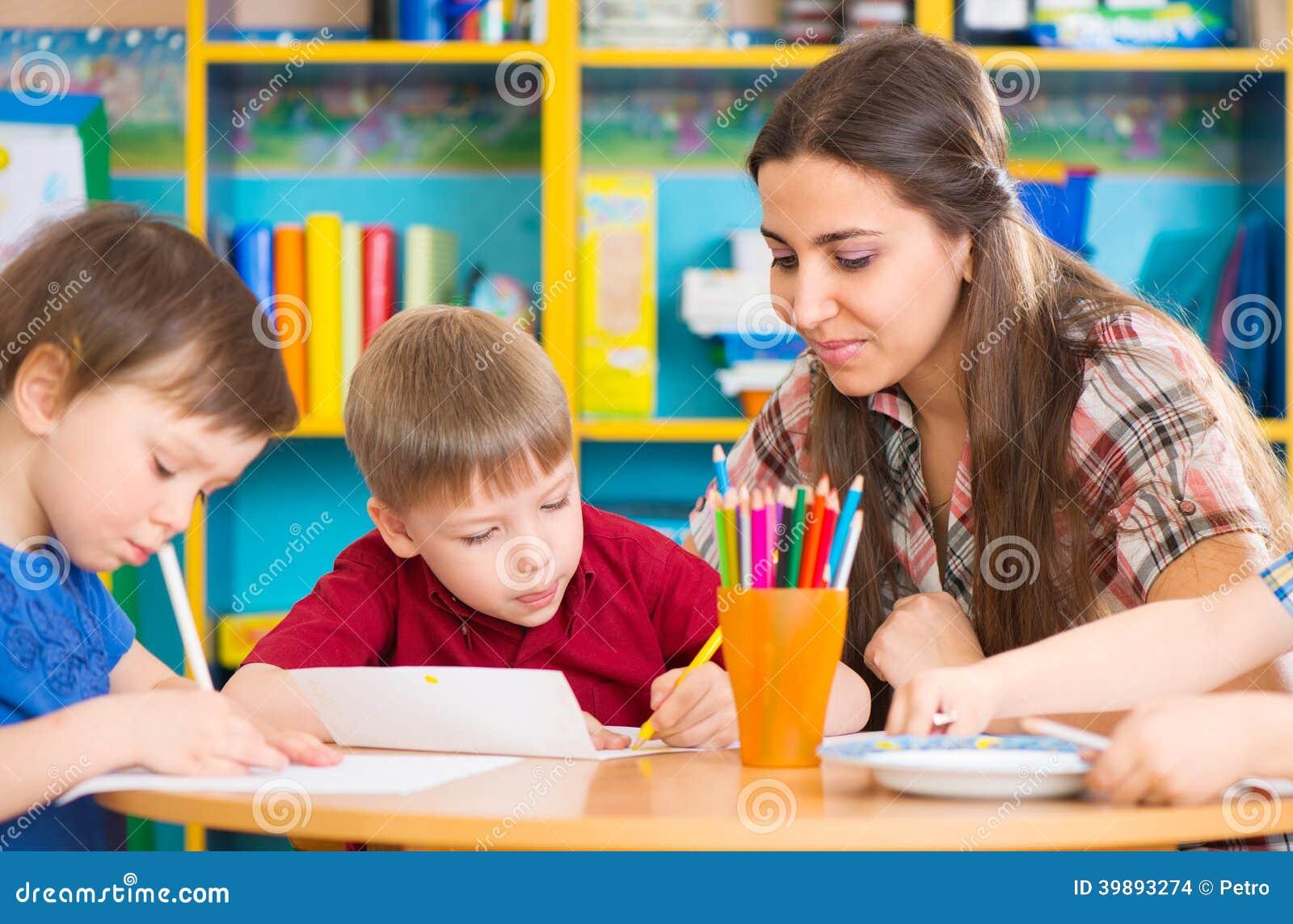 Gulliga barn som drar med läraren på förskole- grupp