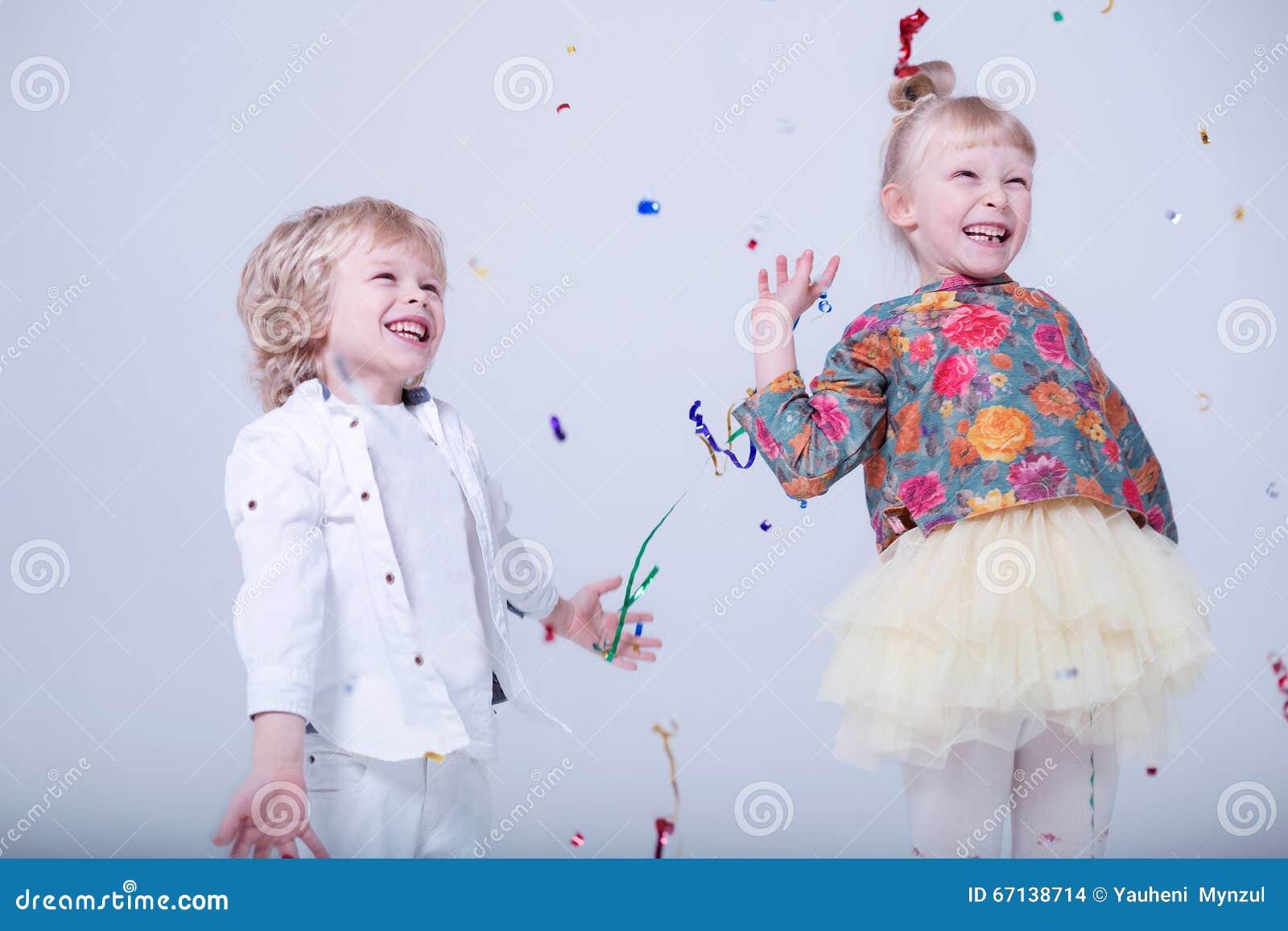 Gulliga blonda barn i en vit studio
