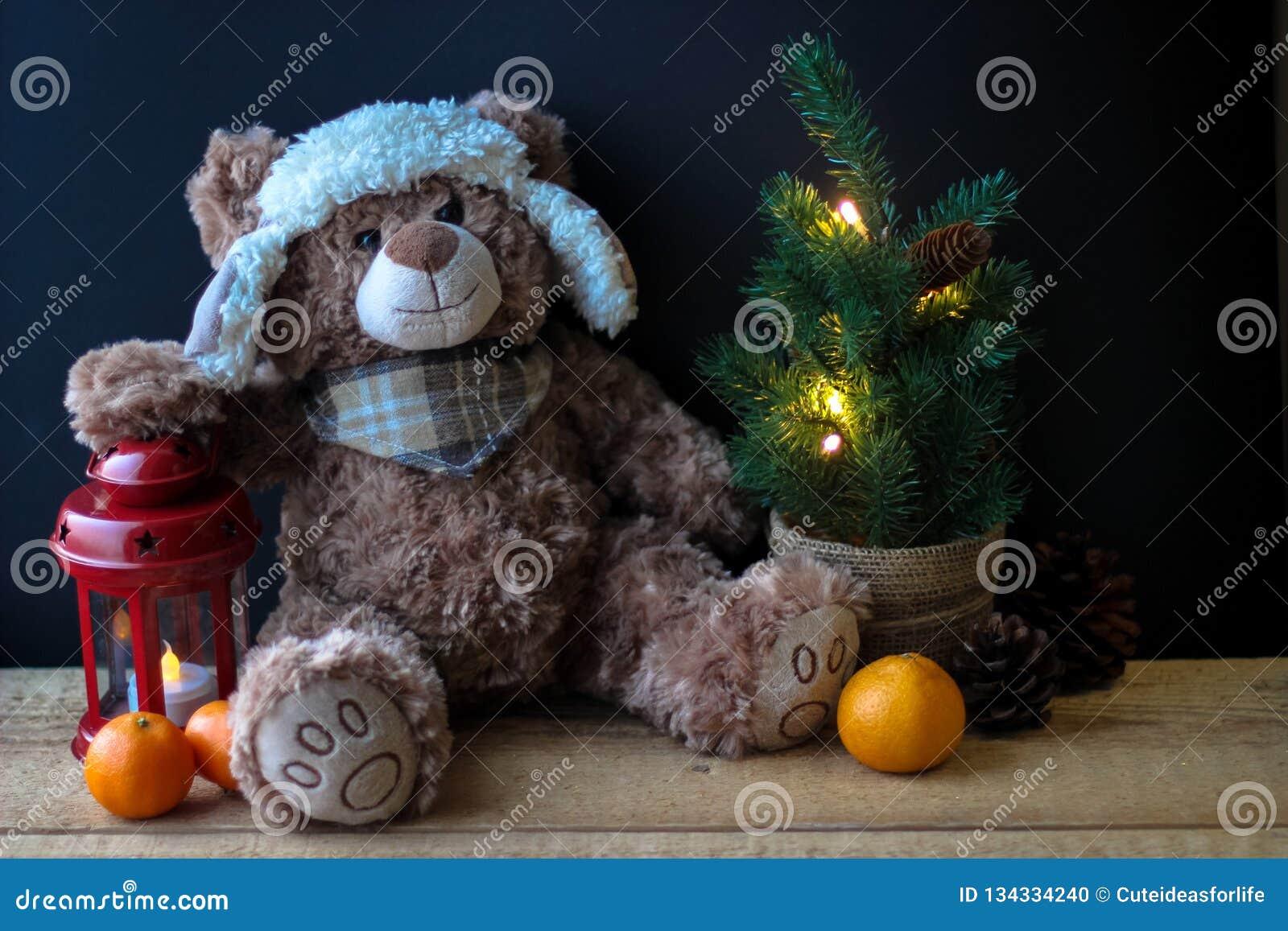 Gulliga den leksakbjörnen som rymmer, tafsar på en röd lykta på en svart bakgrund I ramen kan du se en liten julgran med
