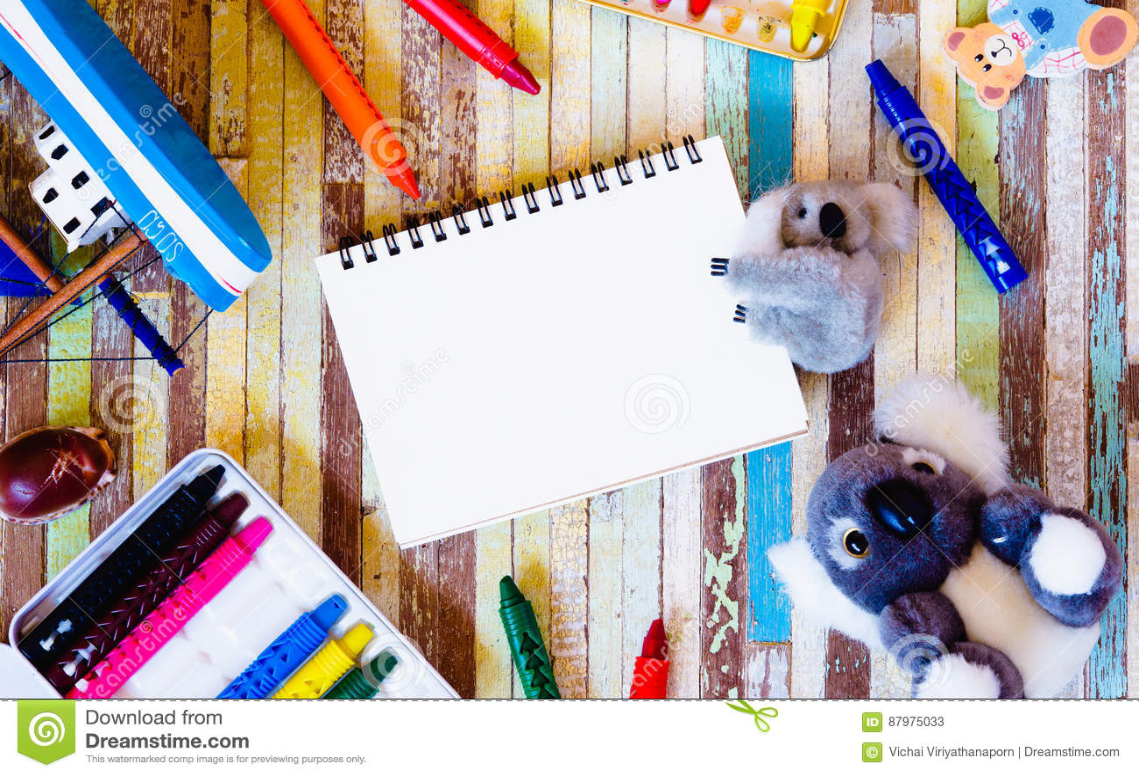 Gulliga dockor med mellanrumet öppnar anteckningsboken och färgpennor på träbackg