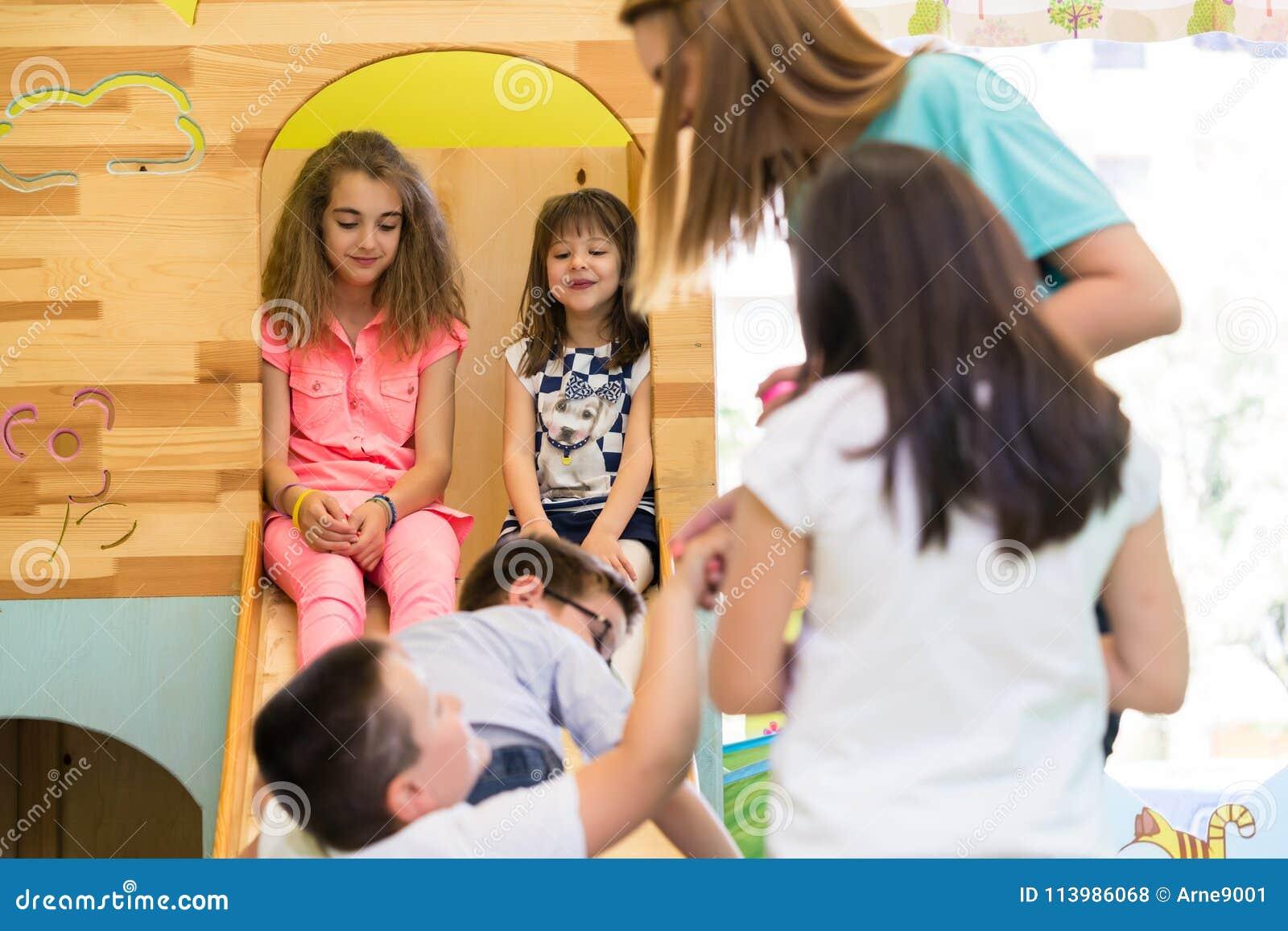 Gulliga flickor som ler under rast som övervakas av en ung lärare