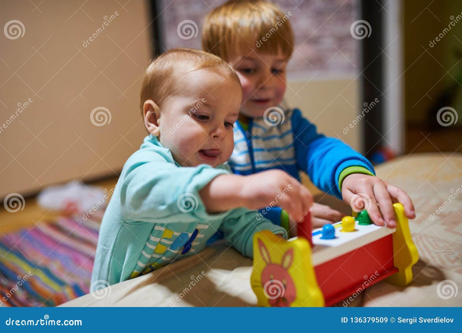 Gulliga pyser som spelar med leksaker vid hemmet