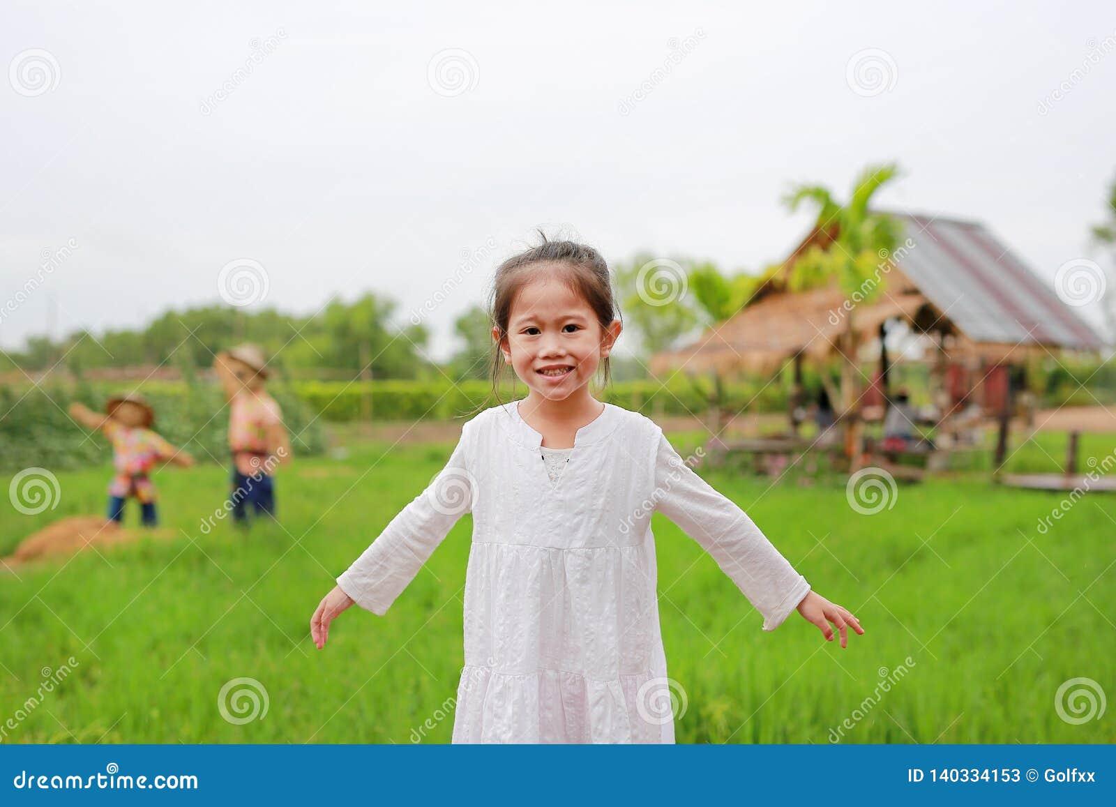 Gulliga små asiatiska flickaelasticitetsarmar på de nya gröna risfältfälten