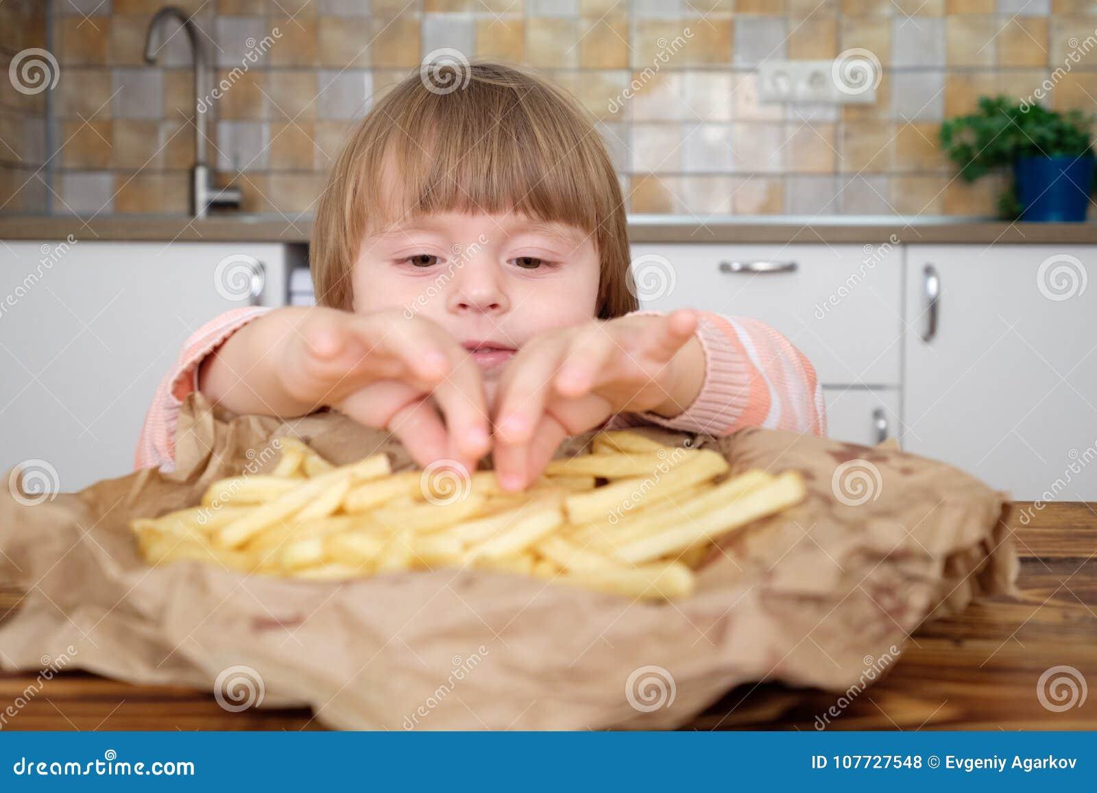 Gulliga små behandla som ett barn flickan som tycker om franska småfiskar på kök
