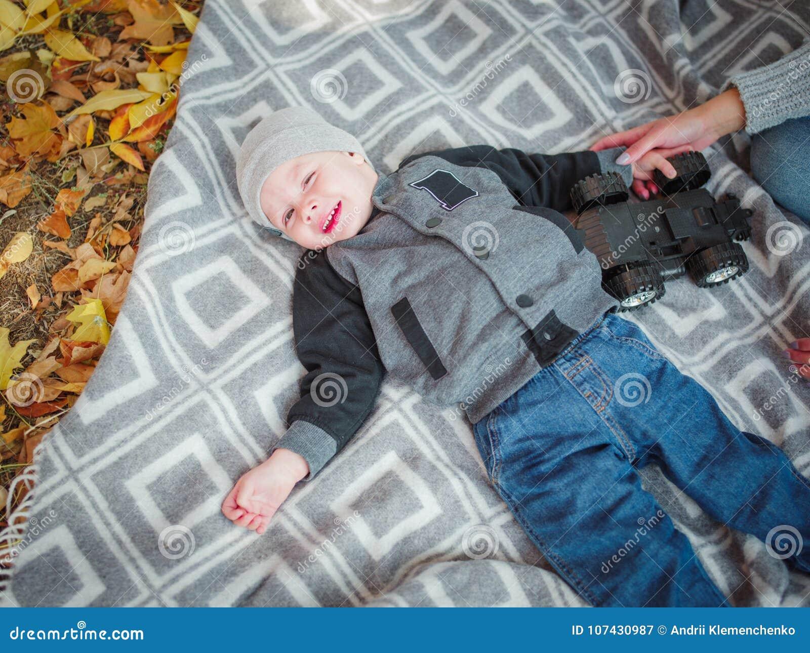 Gulliga små behandla som ett barn pojken som ligger på en filt i en höst, parkerar