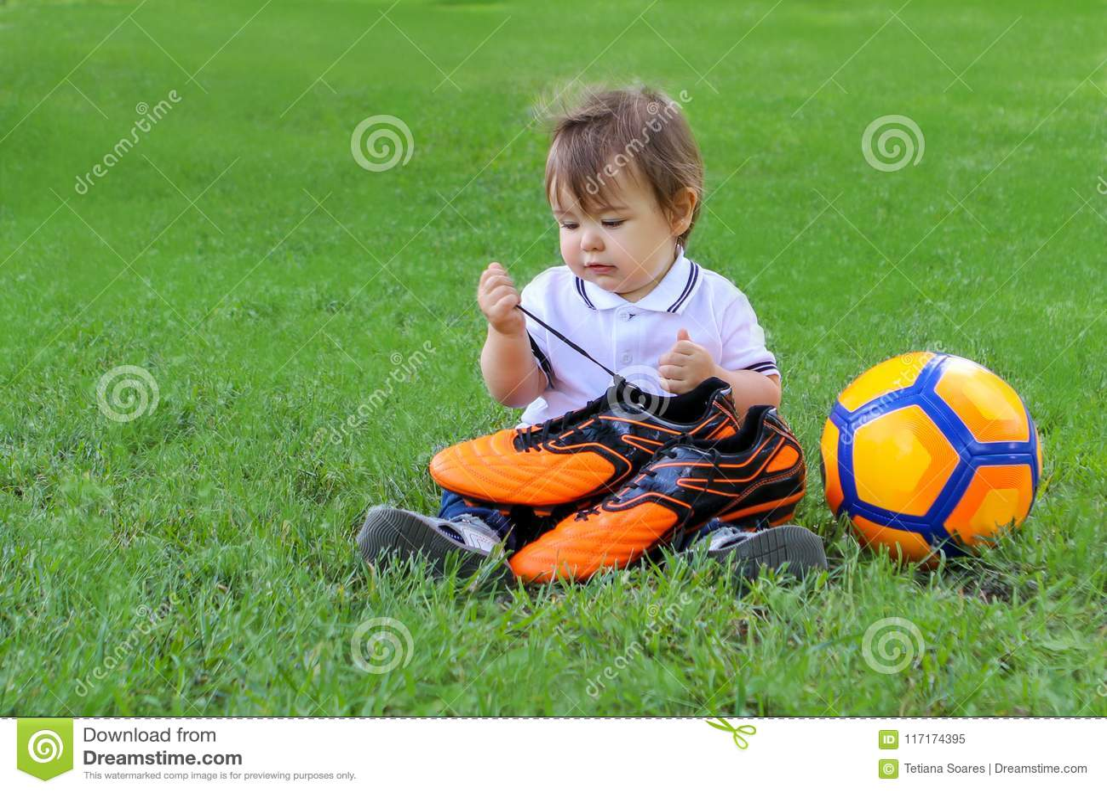 Gulliga små behandla som ett barn pojkesammanträde med oragefotbollbollen på hållande fotbollkängor för grönt gräs i hans händer