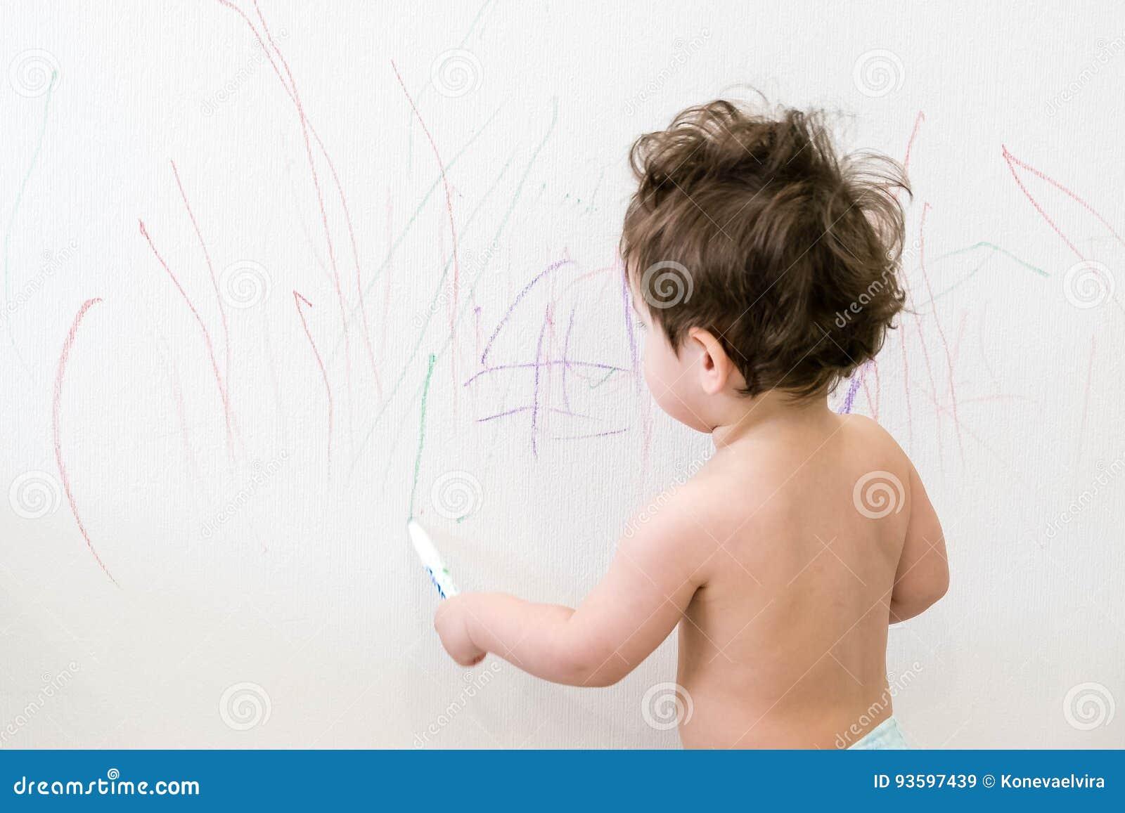 Gulliga små behandla som ett barn pojketeckningen med färgpennafärg på väggen Arbeten av barnet Arbeten av barnet Caucasian årigt