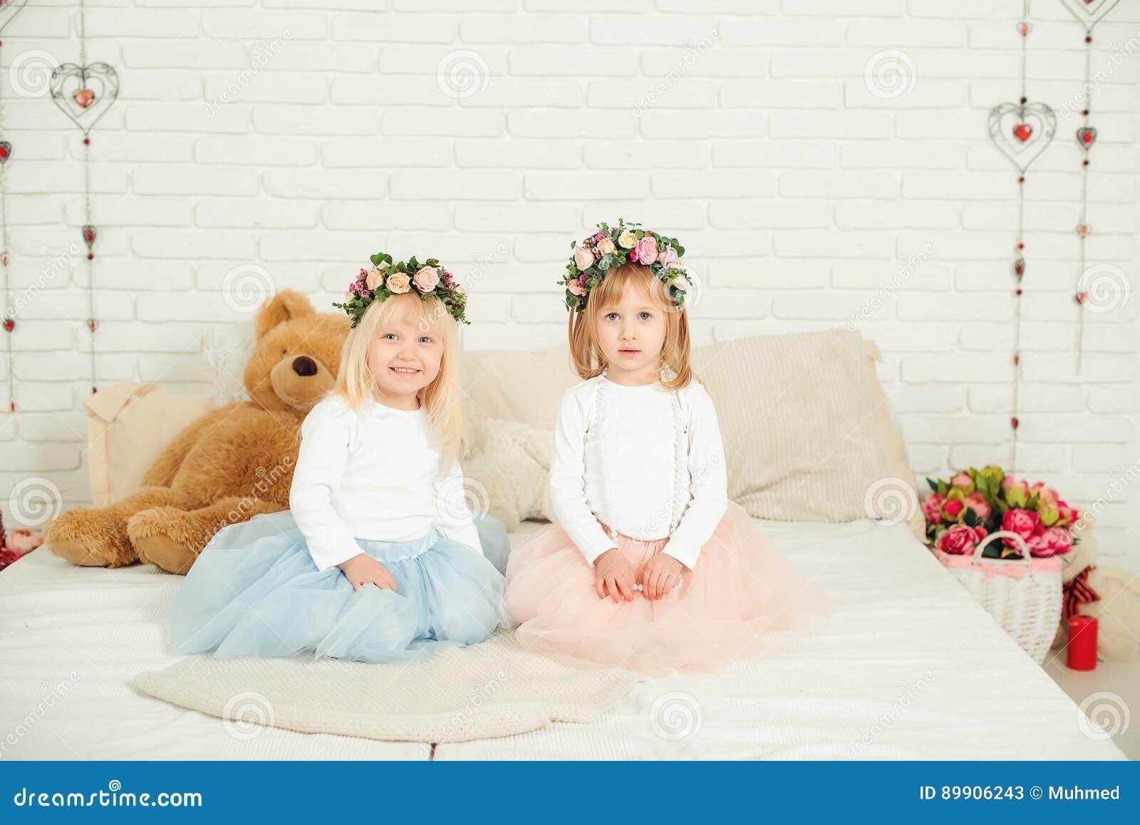Gulliga små flickor i klänningar med blommakransen på deras huvud Två lilla systrar som sitter på sängen i den vita studion