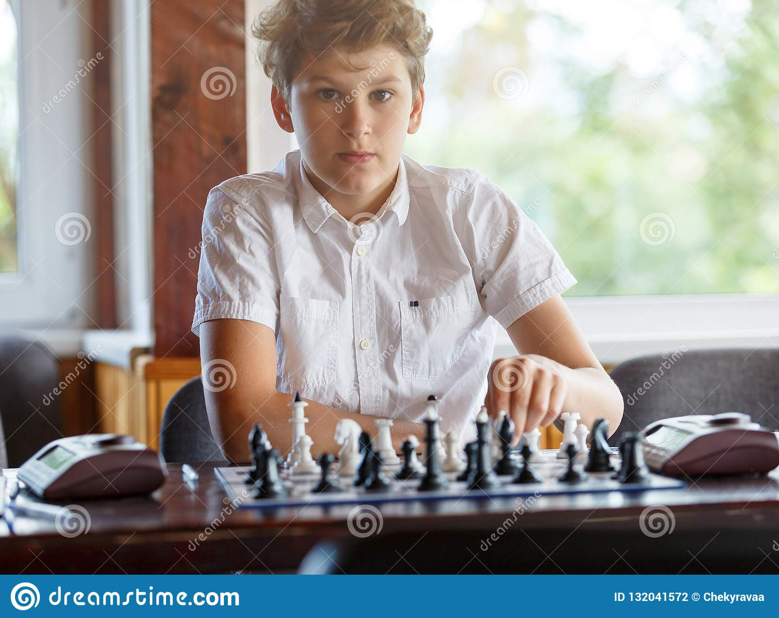 Gulliga smart, sitter spelar 11 år gammal pojke i den vita skjortan i klassrumet och schack på schackbrädet Utbildning kurs, hobb