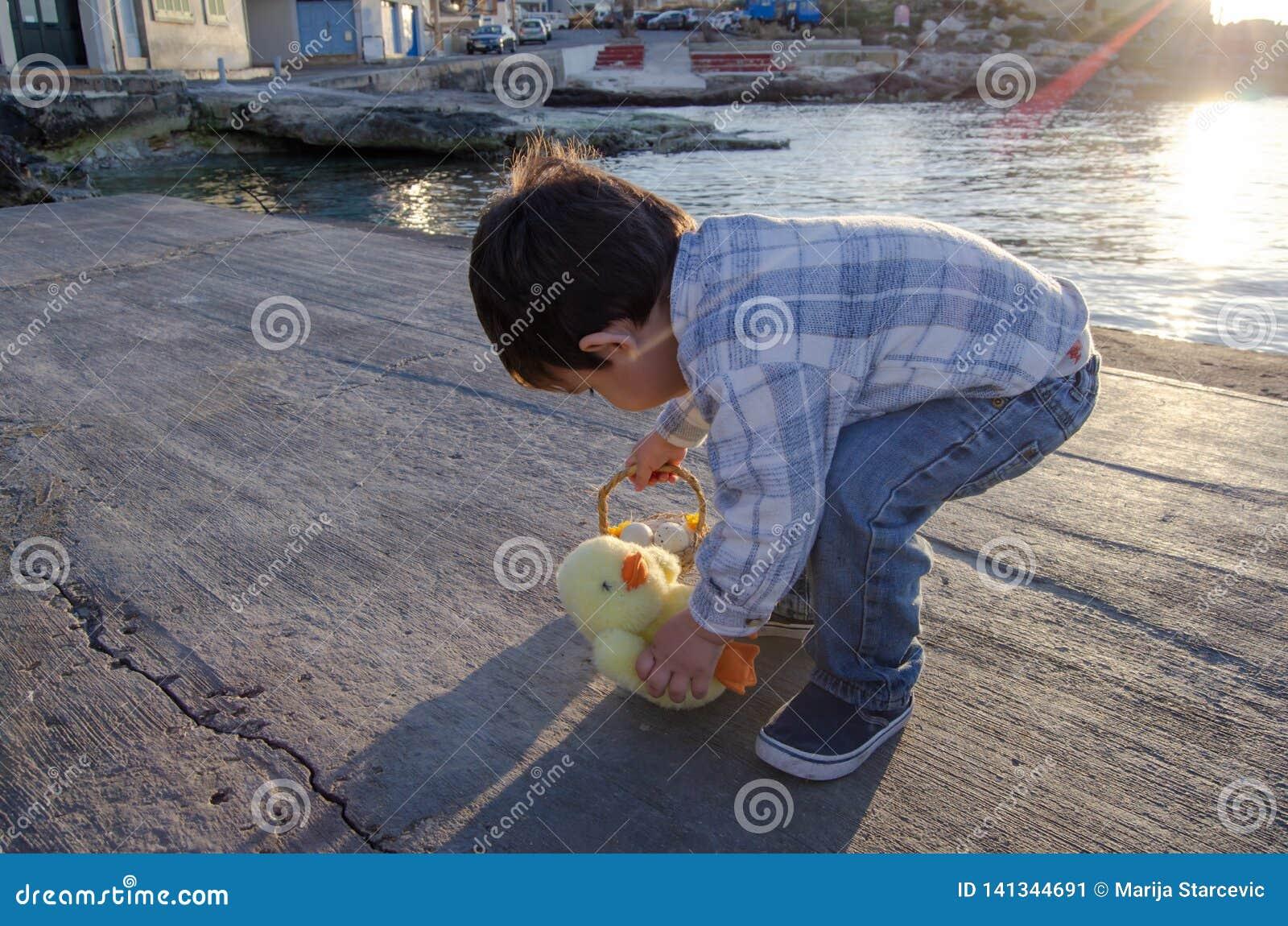 Gulliga två år gammalt litet barn som spelar med den lilla fega leksaken och korgen med två easter ägg på havet doc