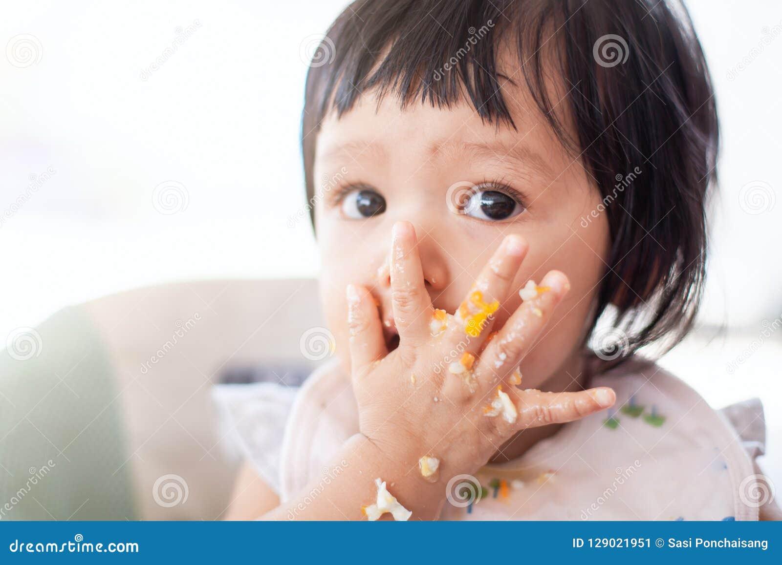 Gulligt behandla som ett barn den asiatiska barnflickan som äter sund mat av henne