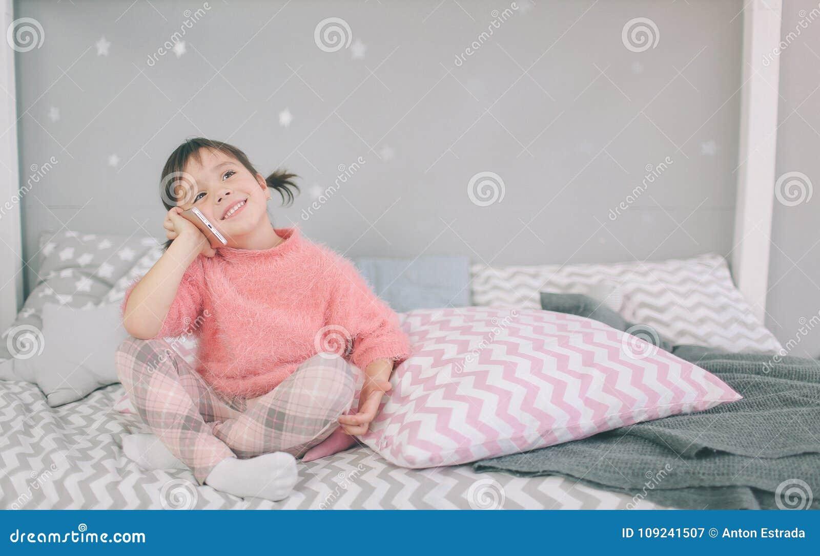 Gulligt behandla som ett barn flickan som spelar en smart telefon, har Smartphone negativ inverkan på dina utveckling och mentala