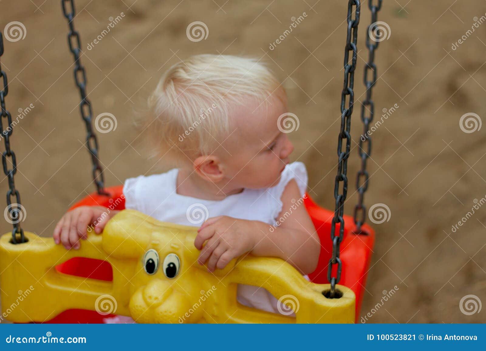 Gulligt blont behandla som ett barn flickasammanträde i en gunga