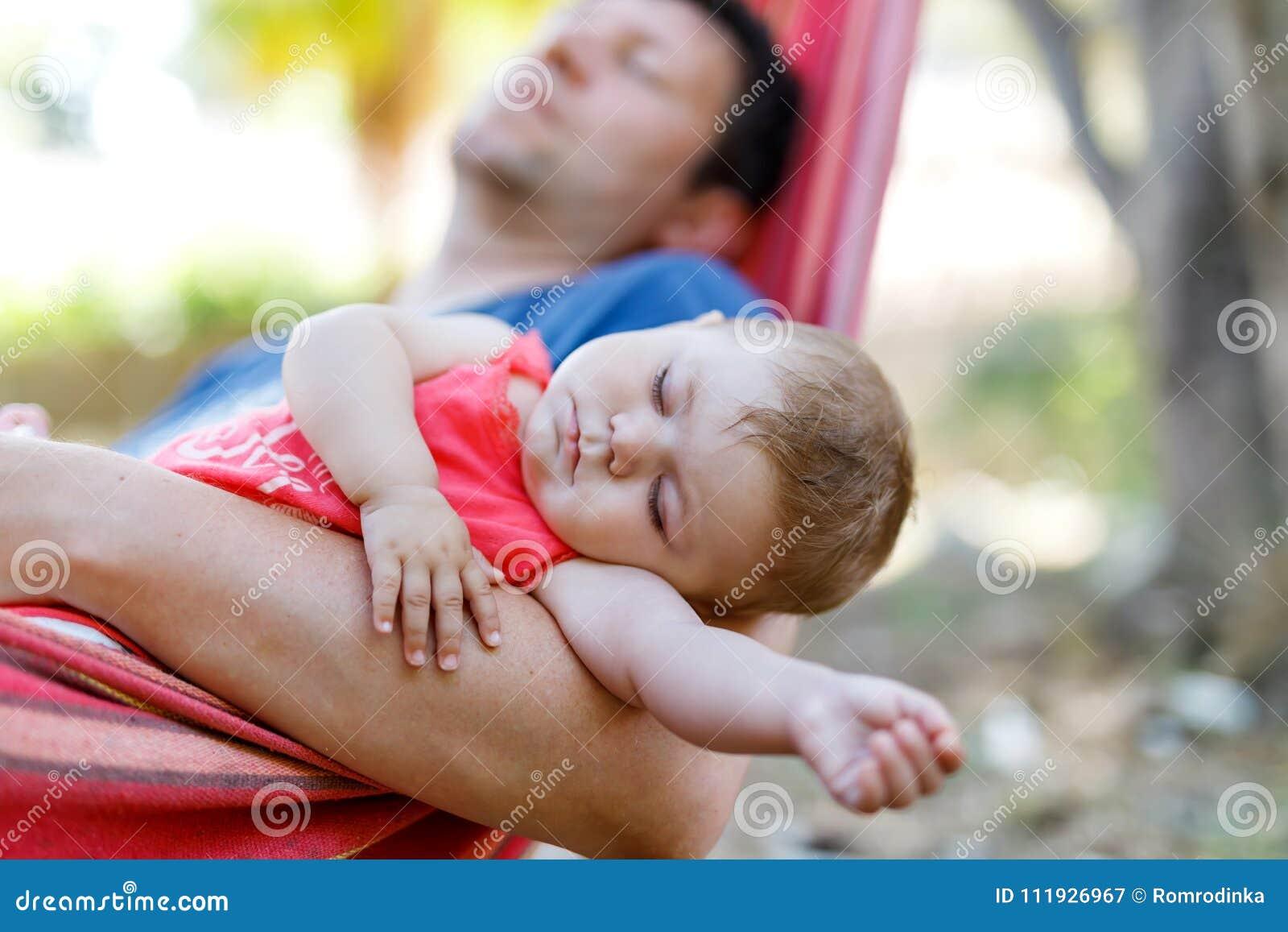 Gulligt förtjusande behandla som ett barn flickan av 6 fridsamma månader och hennes sova för fader i hängmatta i utomhus- trädgår