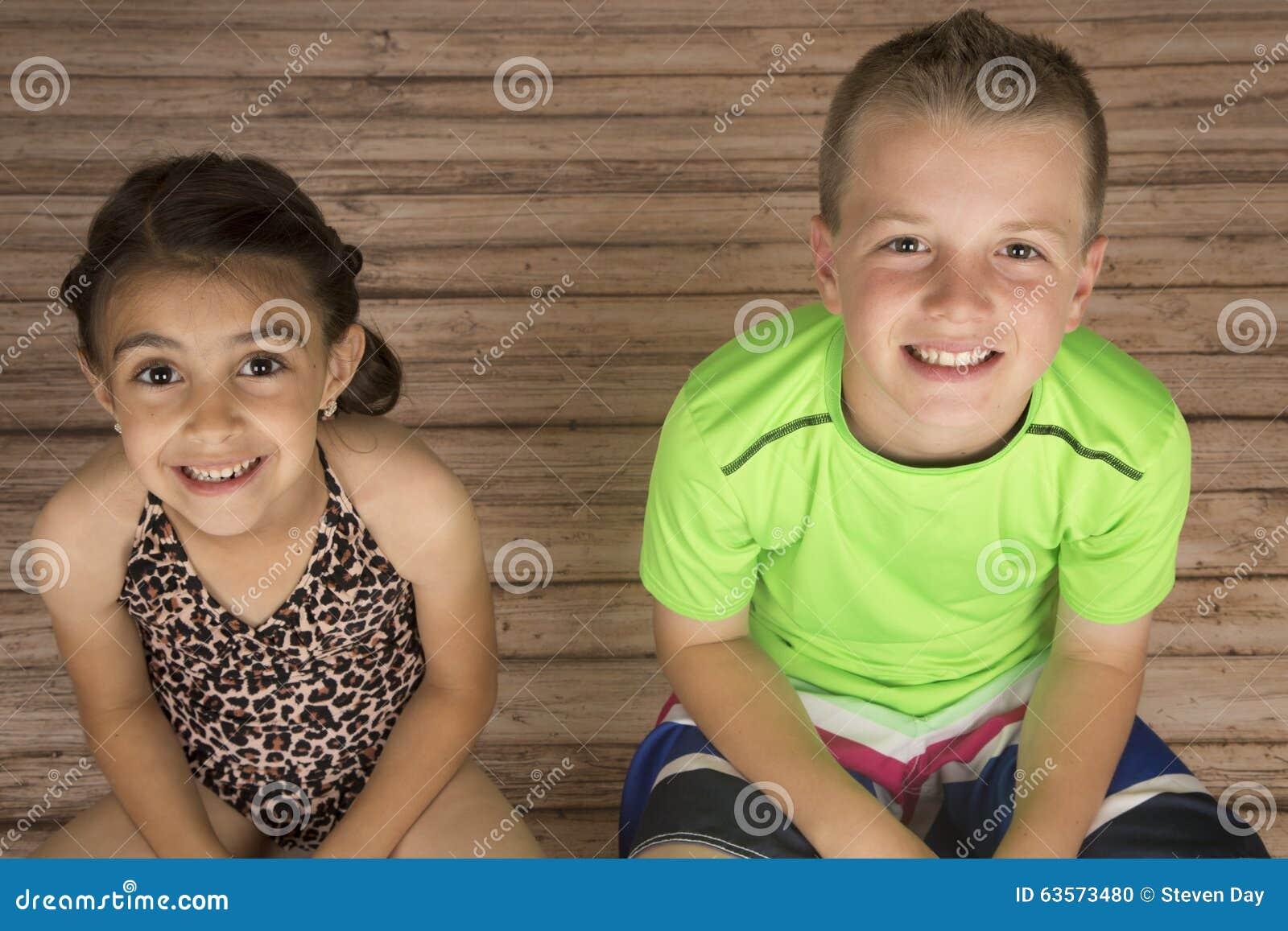 Gulligt flicka- och pojkesammanträde på wood le för golv
