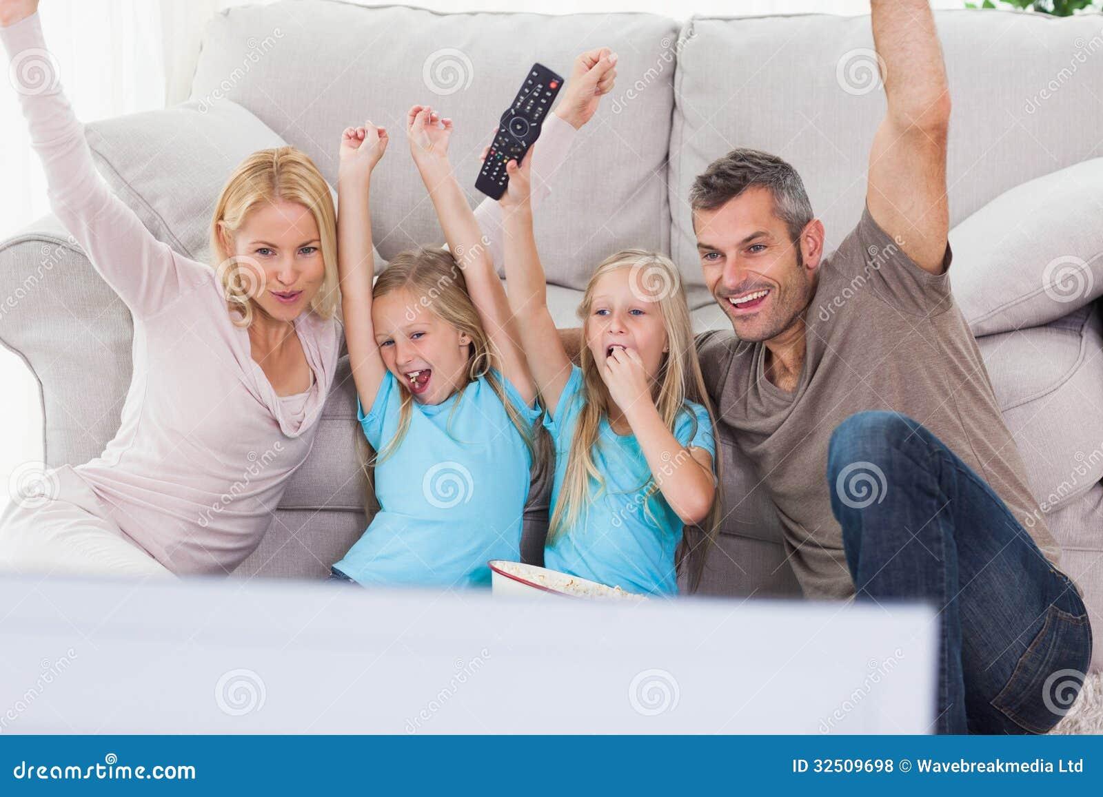 Gulligt kopplar samman och uppfostrar att lyfta armar, medan hålla ögonen på television