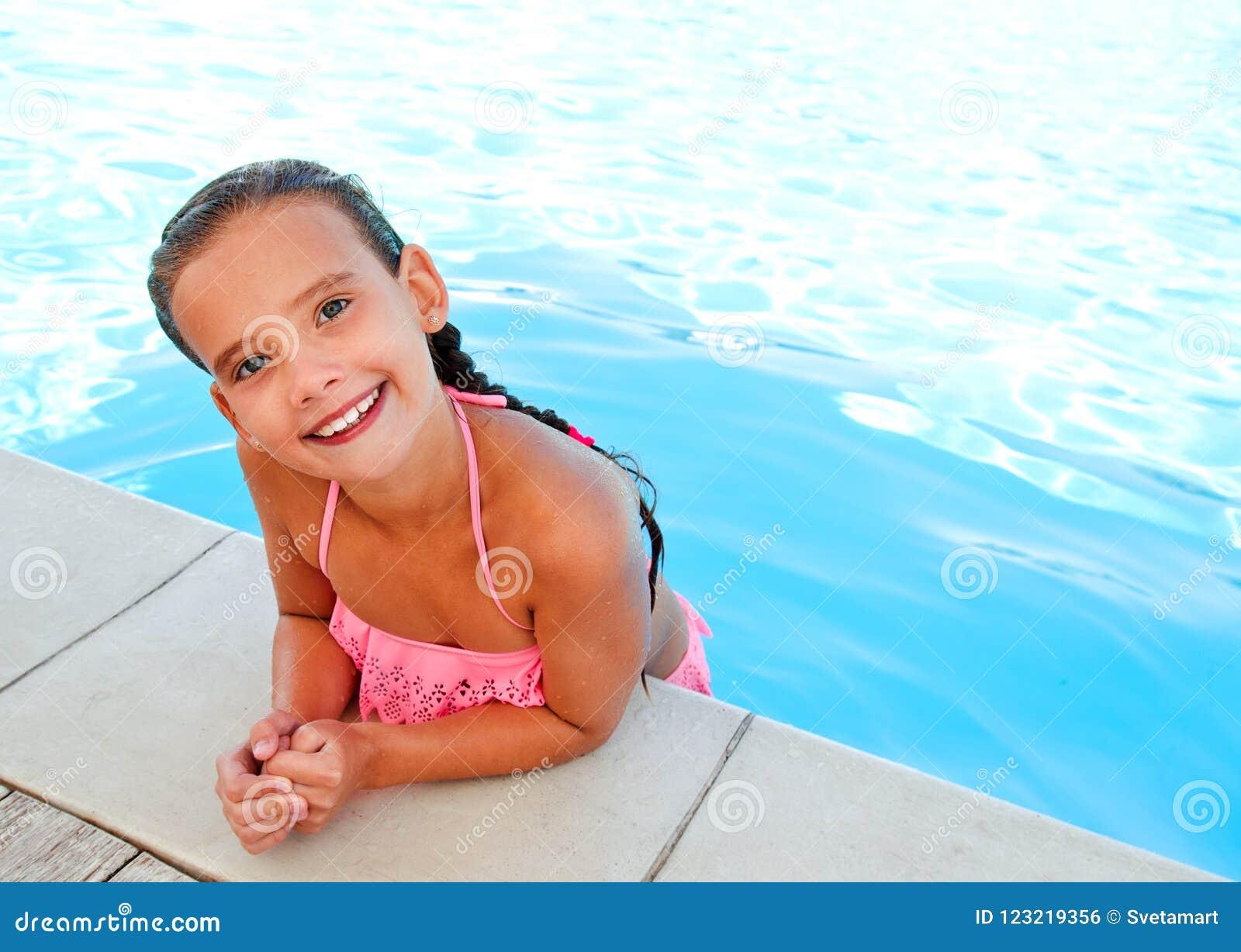 Gulligt le lyckligt liten flickabarn i simbassäng