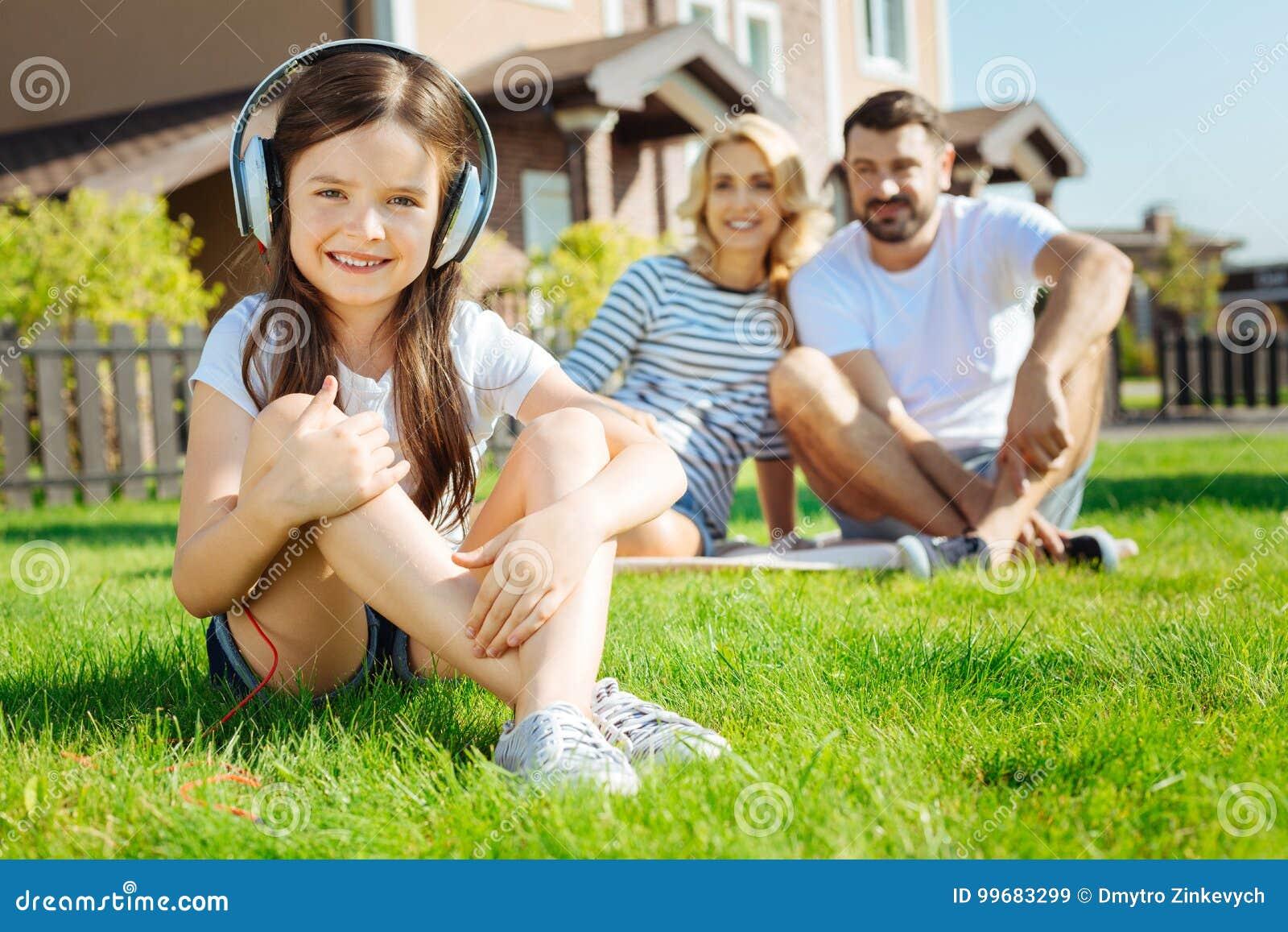 Gulligt liten flickasammanträde på gräs och lyssnande musik