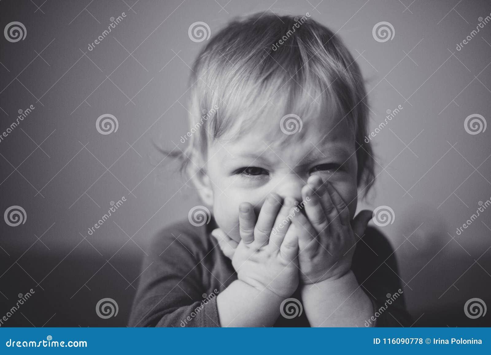Gulligt litet blont behandla som ett barn är bitterly skrik och pressar hans händer till hans framsida close upp