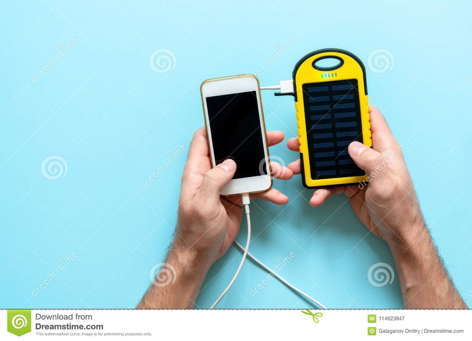 Gult solenergibatteri av en apparat på en blå bakgrund i händerna av en man