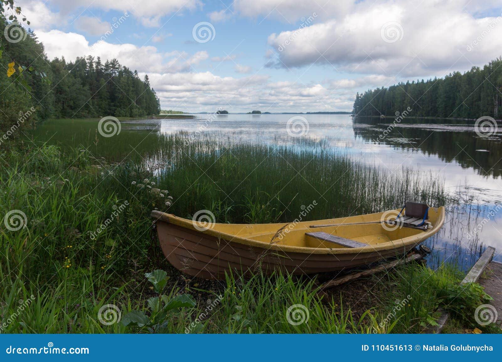 Gult träfartyg på kusten av en pittoresk sjö