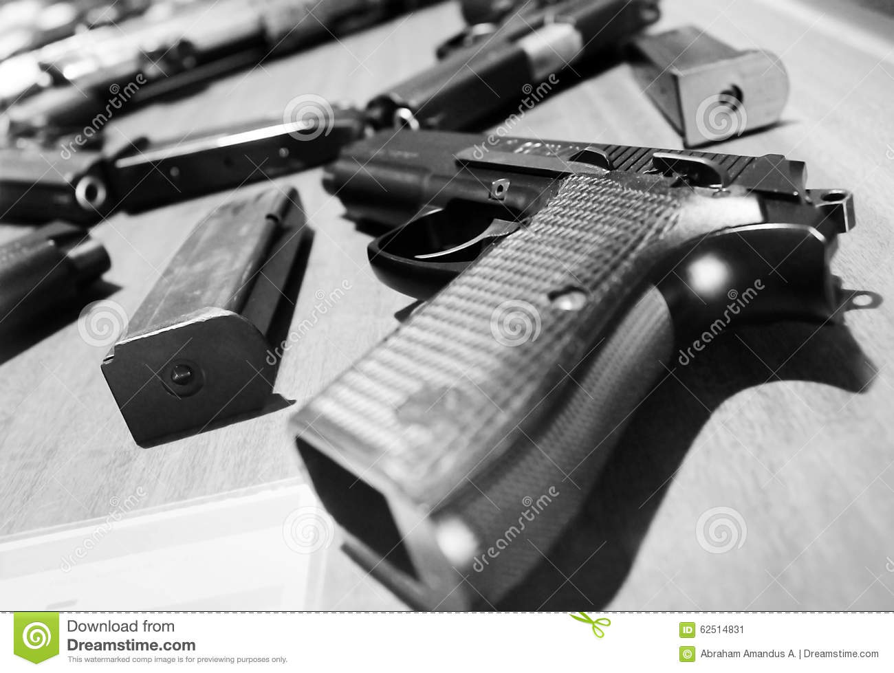 Semi automatic handguns or pistols and its magazines the gun at the near side is a pistol which made in indonesia black and white photography