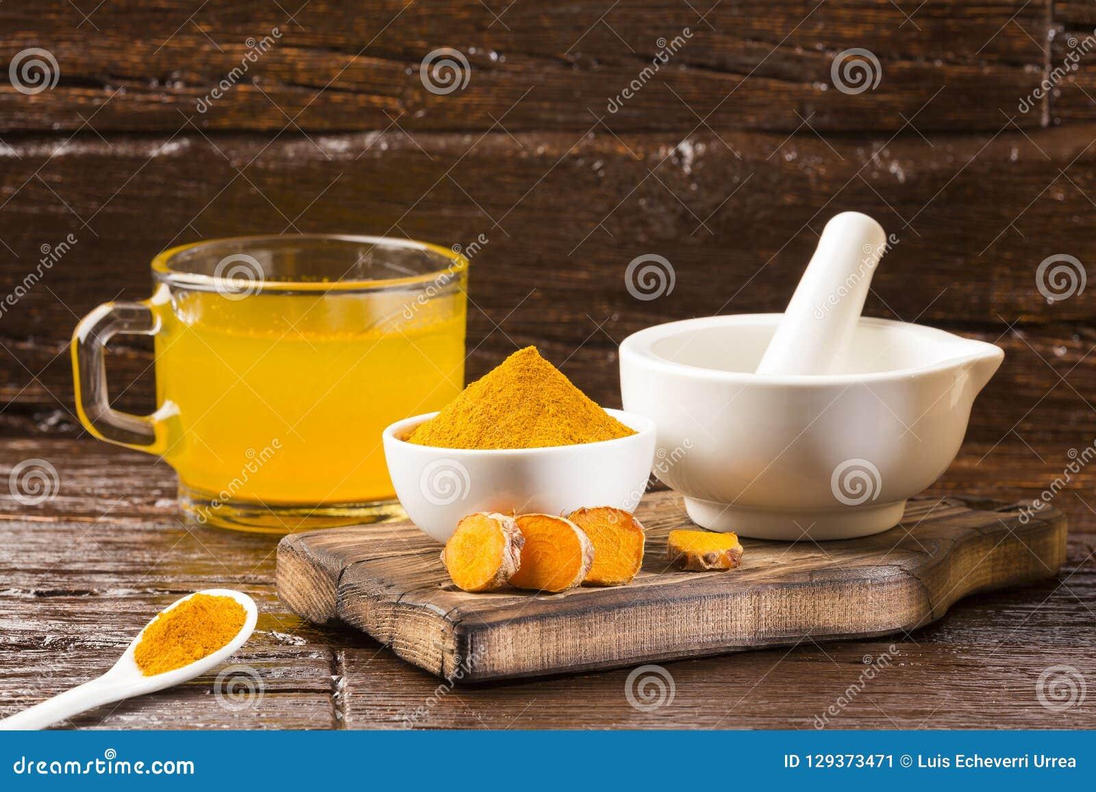 Gurkmeja och vatten, sund drink - träbakgrund