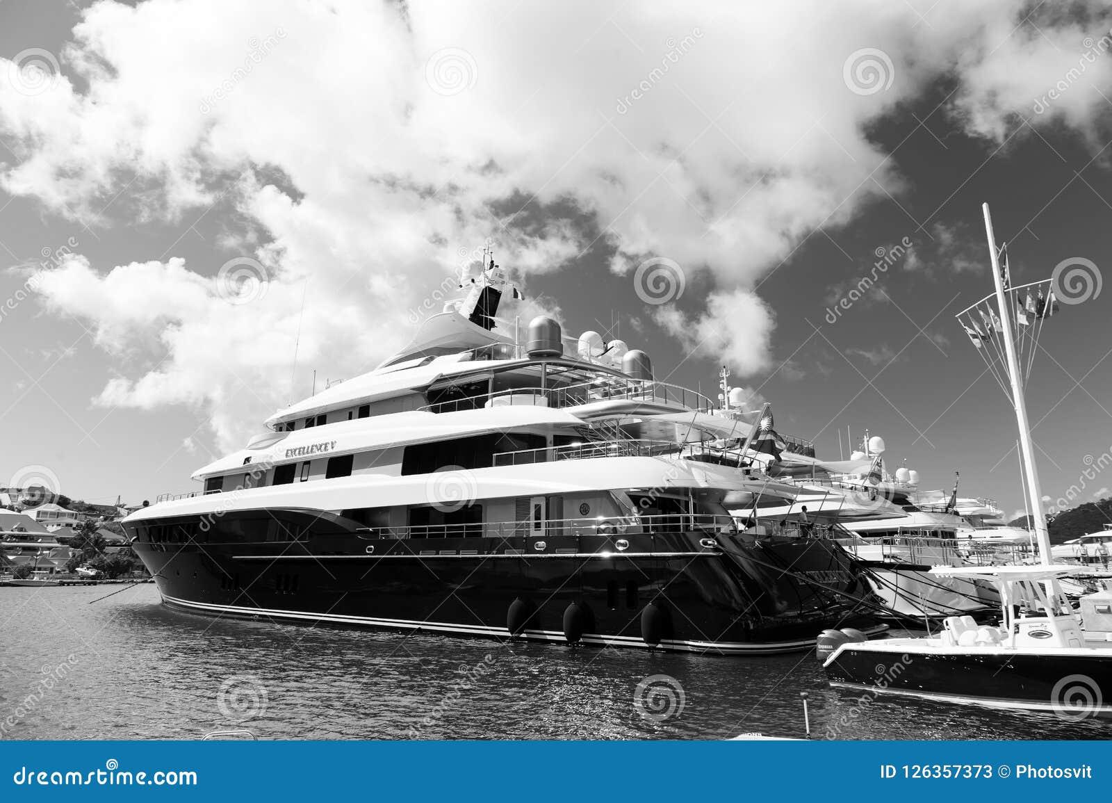 Gustavia, stbarts - 25 de enero de 2016: transporte y buque del agua Yates anclados en el embarcadero del mar en la playa tropica