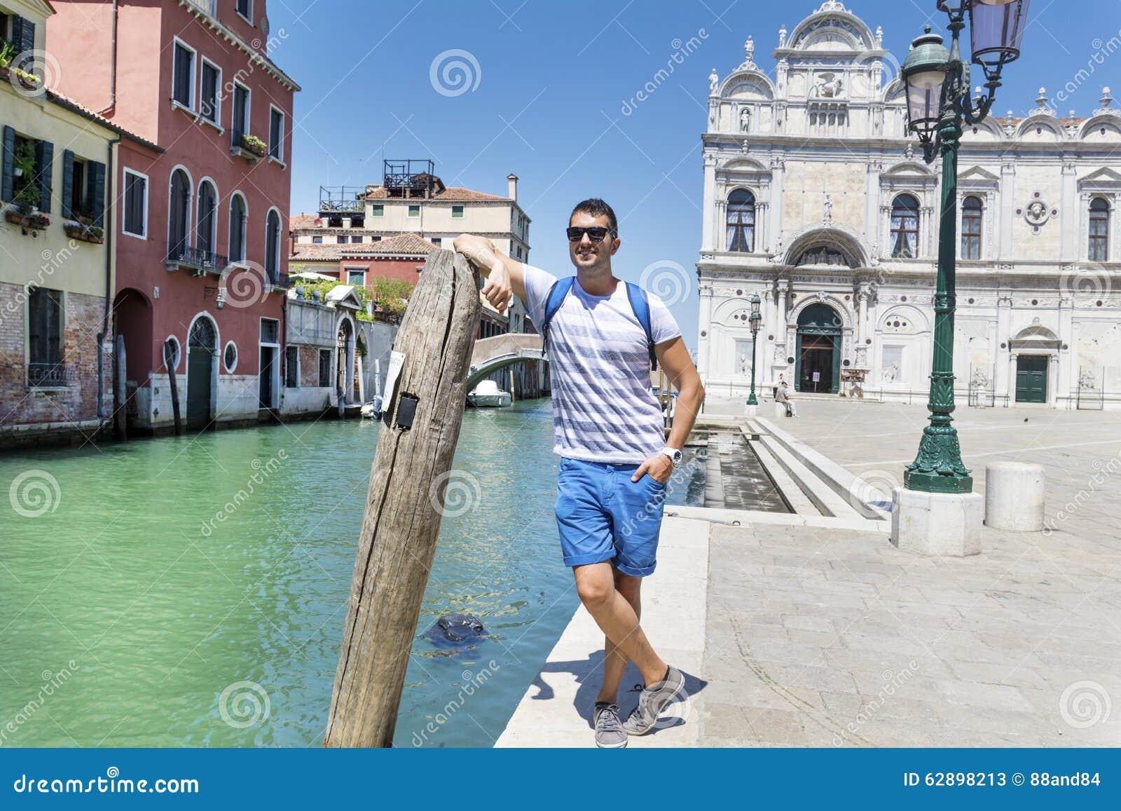Gut aussehender Mann, der auf Brücke in Venedig, Italien steht